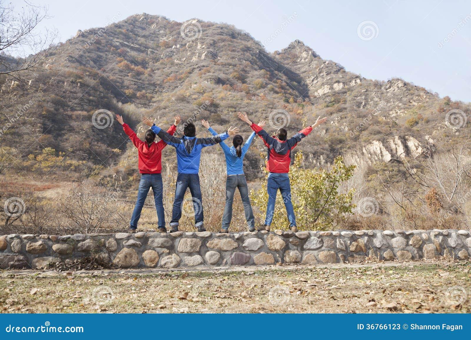 Groep jongeren die zich op de richel, uitgestrekte wapens bevinden