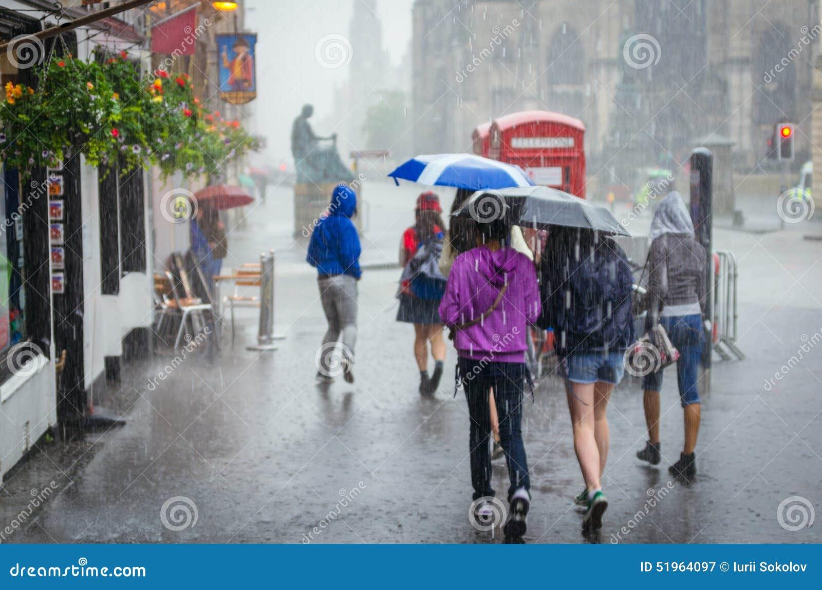 Groep meisjes die bij de zomerregen lopen in de stad