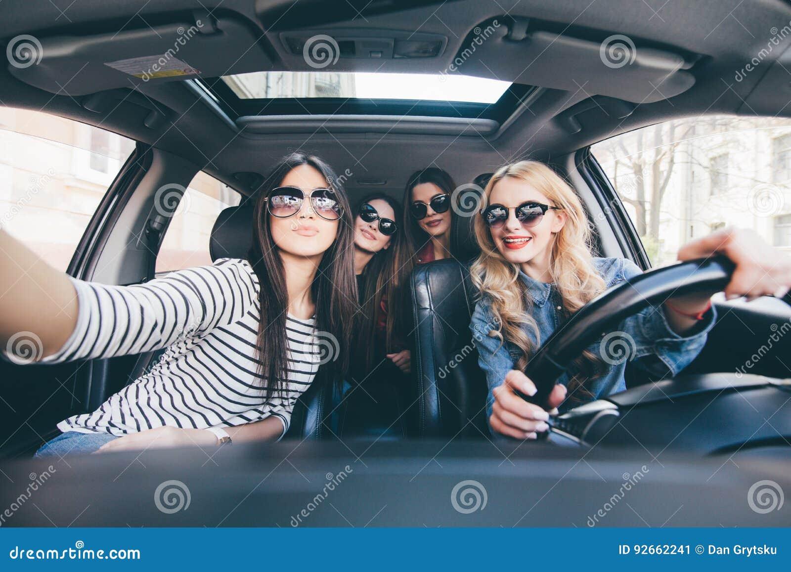 Groep meisjes die pret in de auto hebben en selfies met camera op wegreis nemen