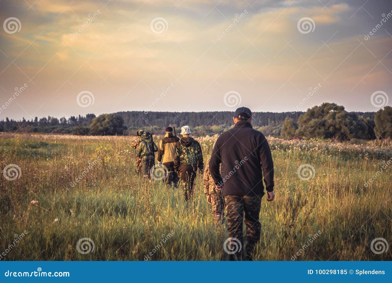 Groep mensen die op een rij door landelijk gebied bij zonsondergang tijdens jachtseizoen in platteland weggaan