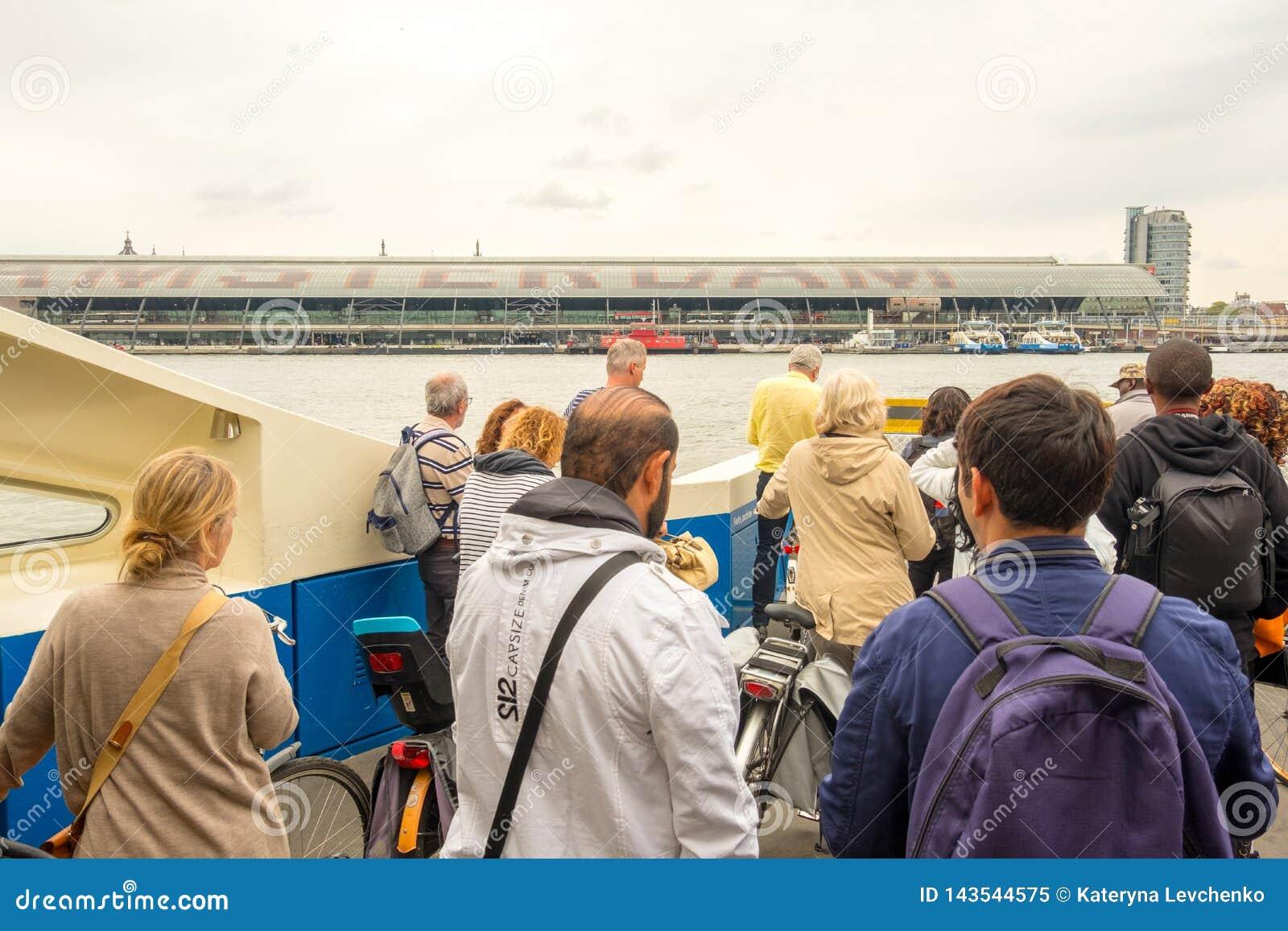 Groep mensen op de rubriek van de passagiersveerboot naar de centrale post in Amsterdam, Nederland