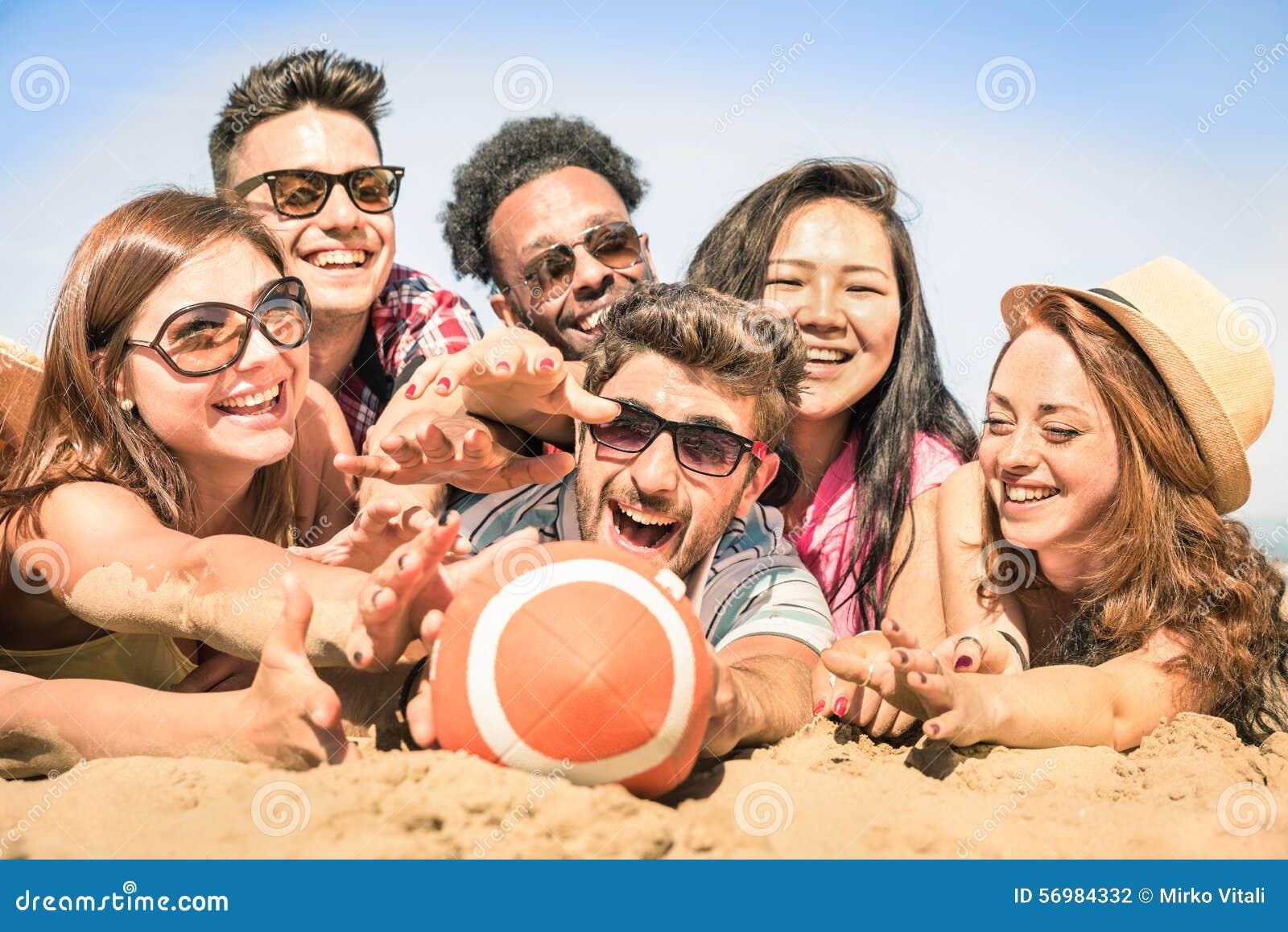 Groep multiraciale gelukkige vrienden die pret hebben bij strandspelen