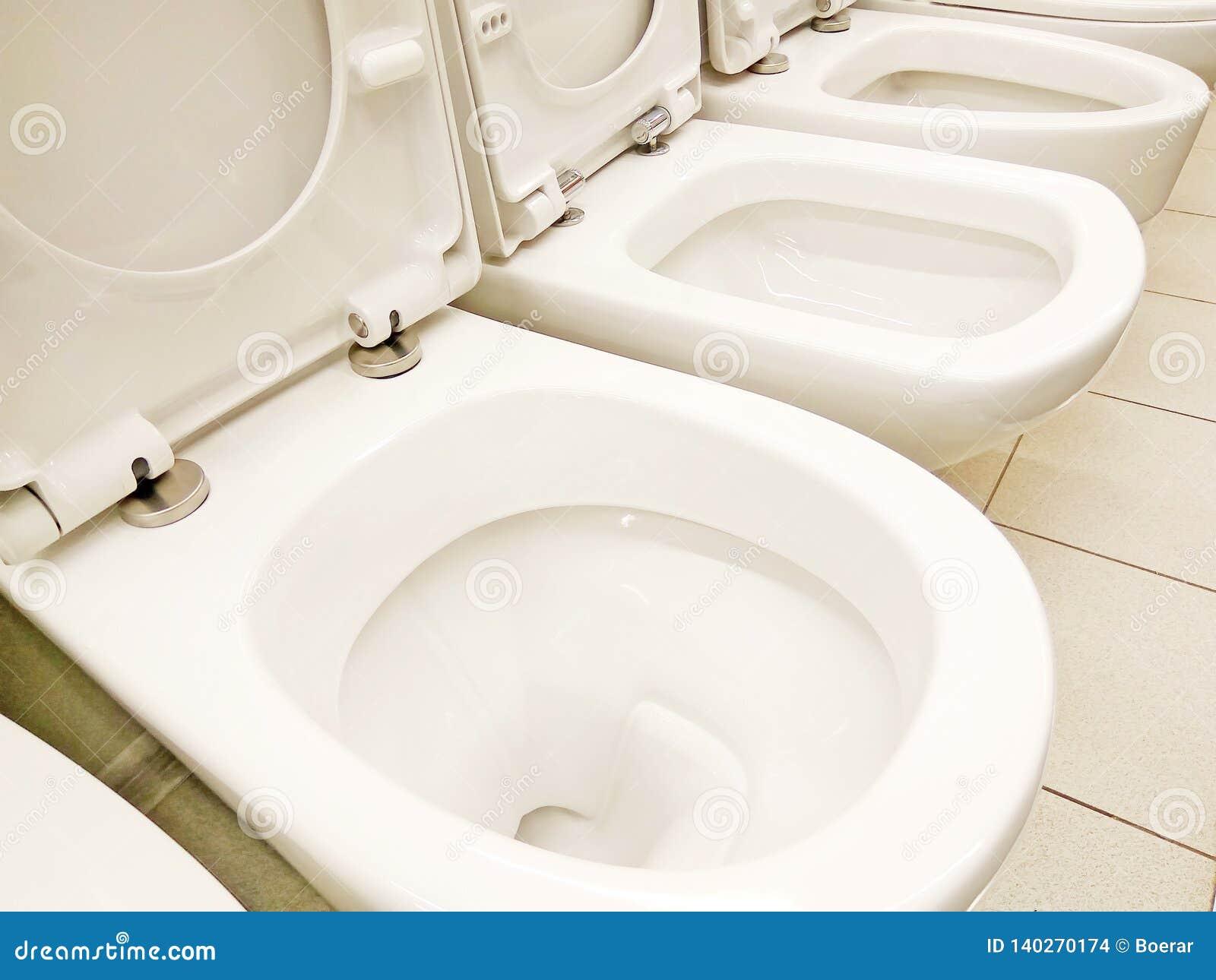 Groep nieuwe schone witte geopende toiletkommen