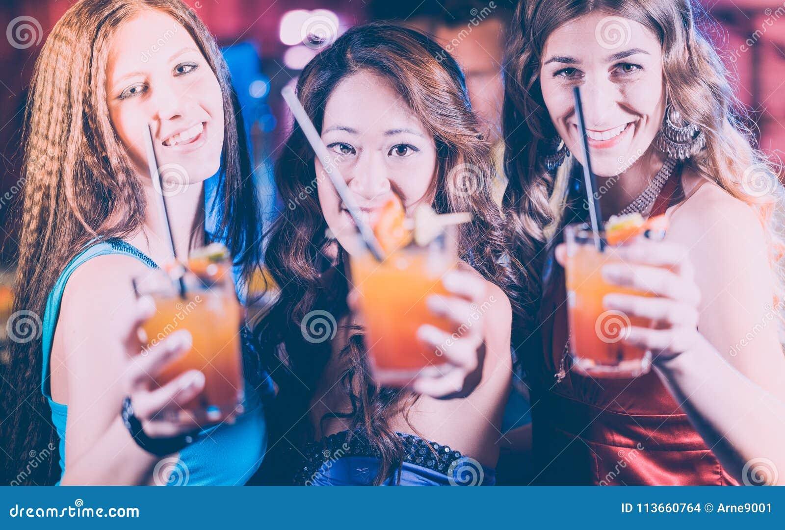 Groep partijmensen - vrouwen met cocktails in een bar of een club