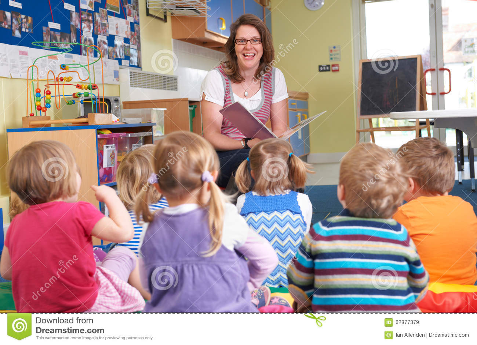 Groep Preschoolkinderen die aan Leraar Reading Story luisteren
