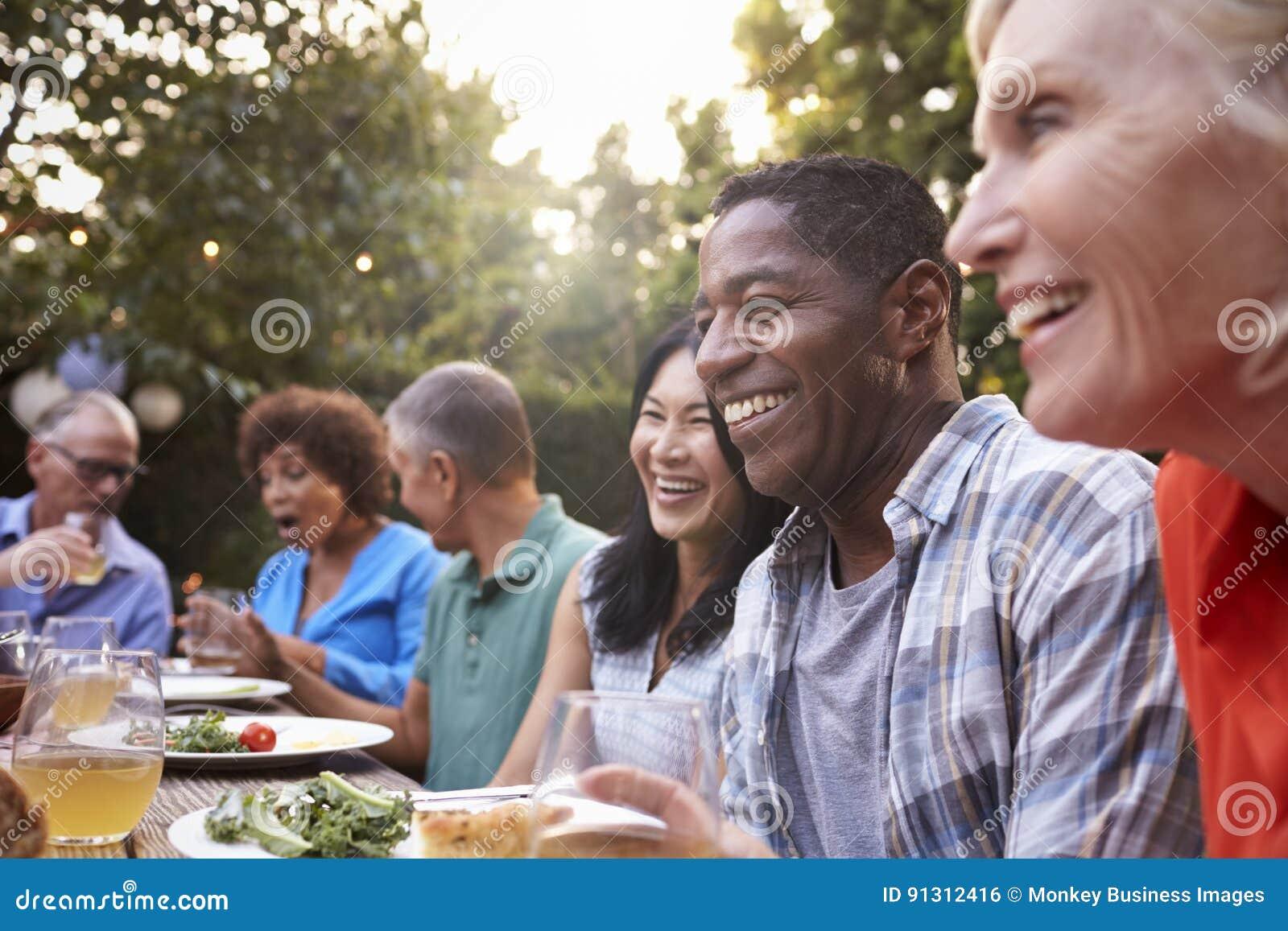Groep Rijpe Vrienden die van Openluchtmaaltijd in Binnenplaats genieten