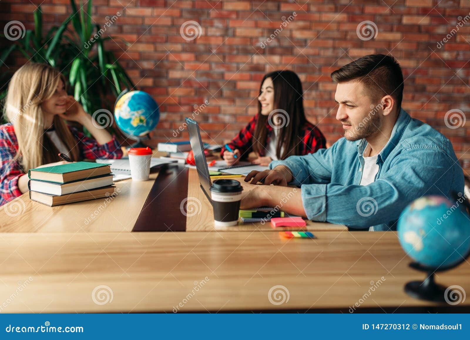 Groep studenten die bij de lijst samen bestuderen