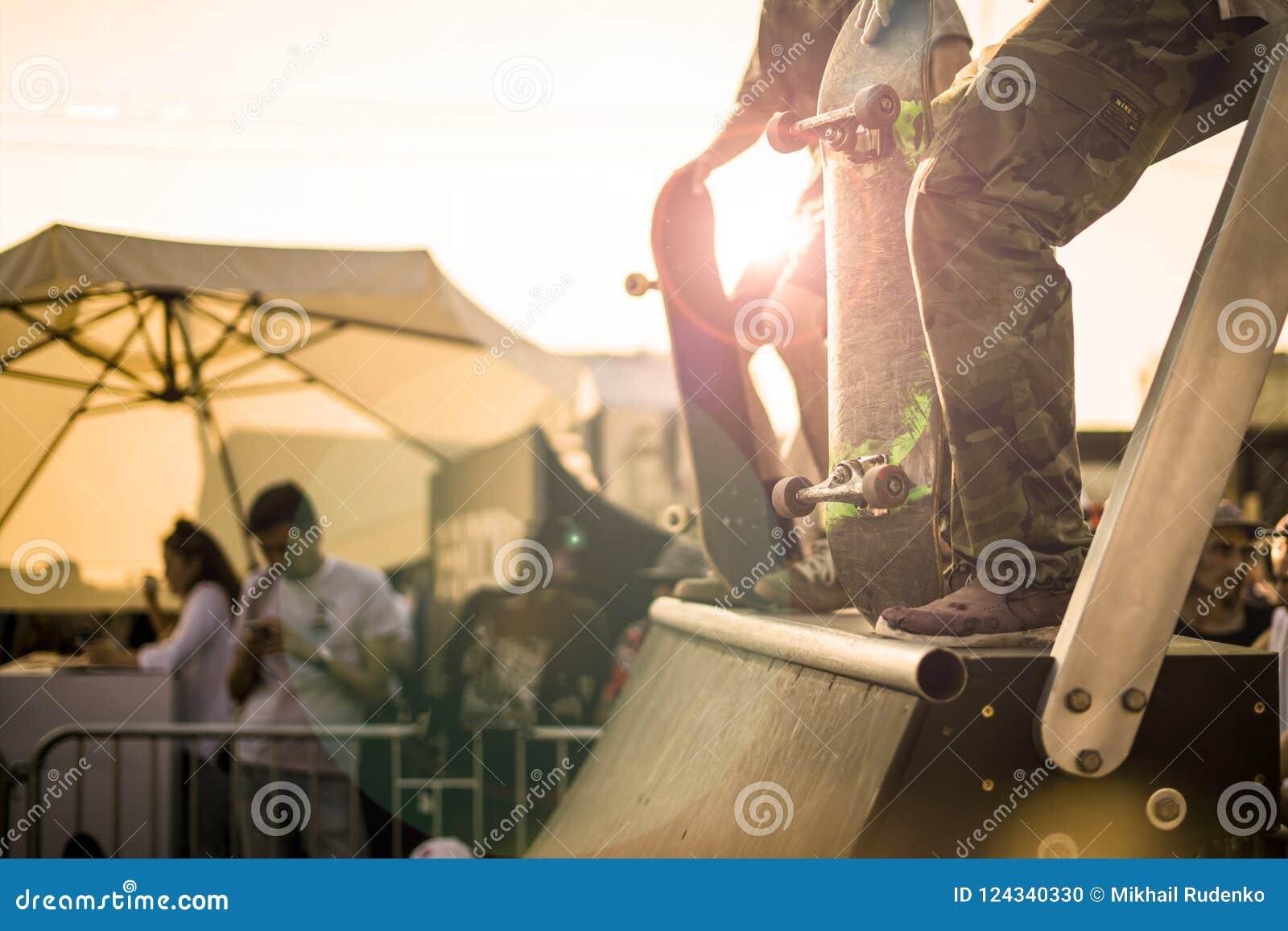 Groep tieners met hun skateboards op de helling die aan de concurrentie tijdens een zonsondergang deelnemen