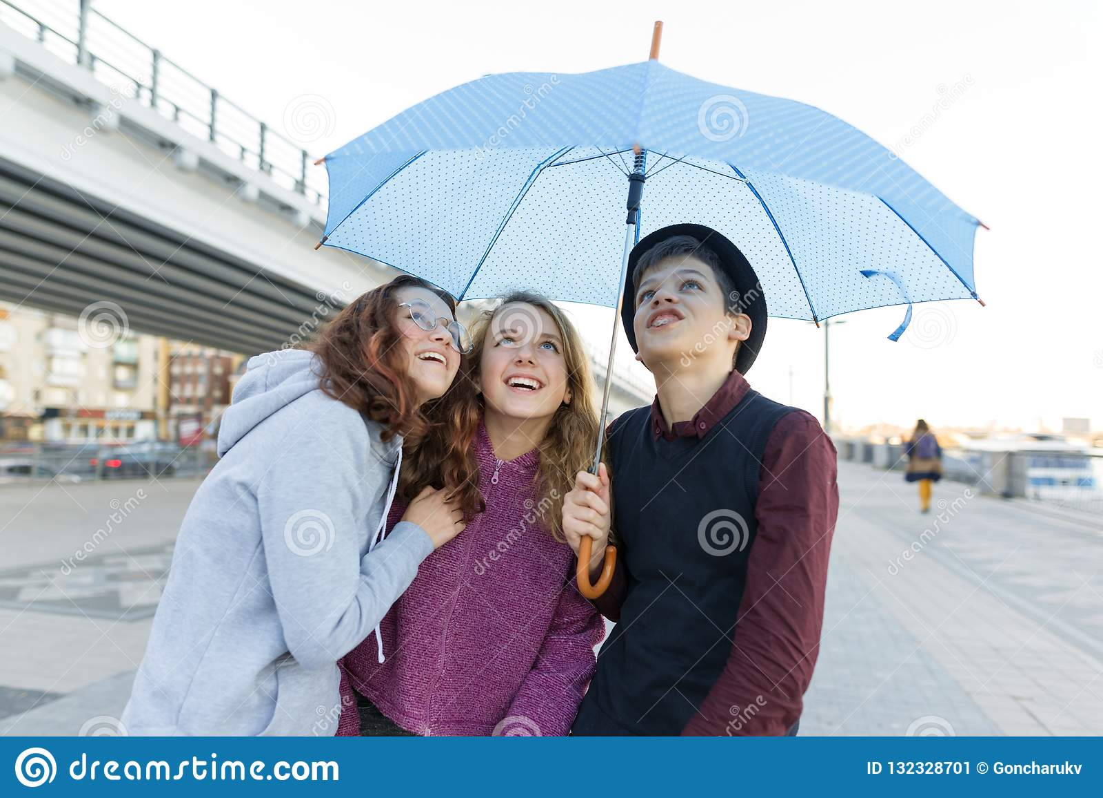 Groep tienersvrienden die pret in de stad, het lachen jonge geitjes met paraplu hebben Stedelijke tienerlevensstijl