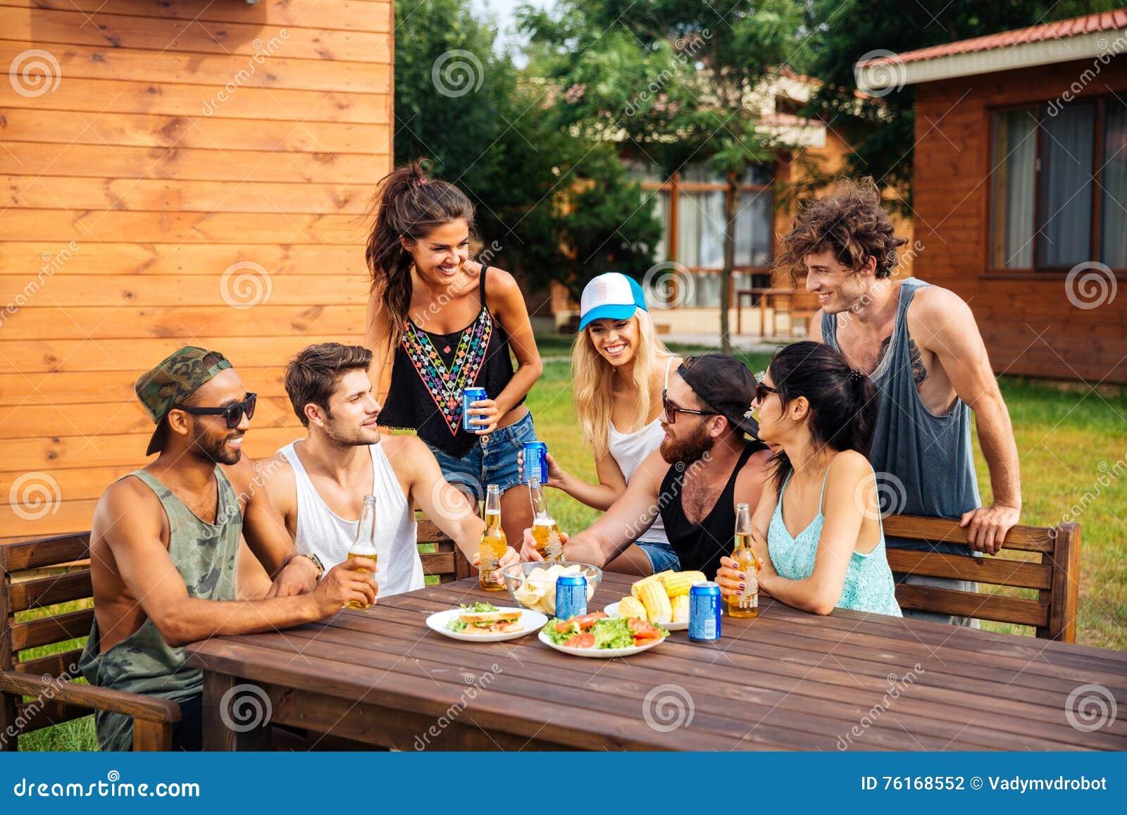 Groep tienervrienden die bier drinken en snacks eten