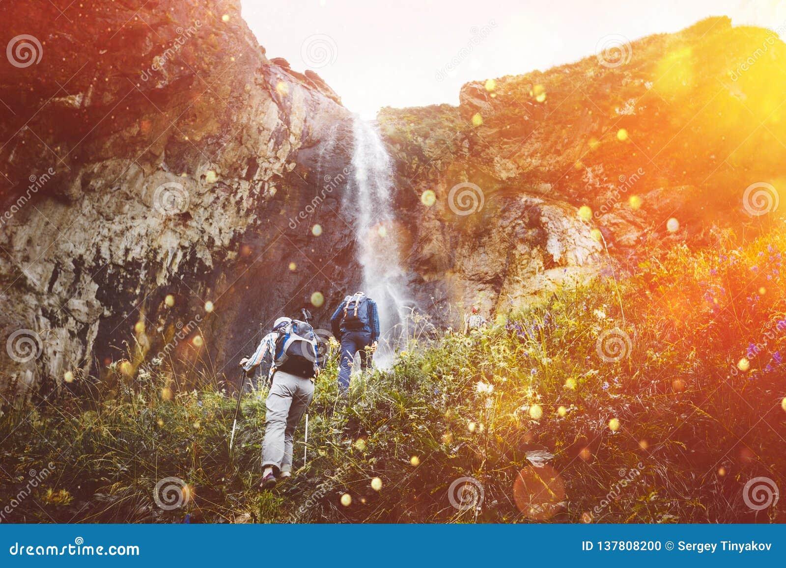 Groep toeristen die bergop aan Waterval met zonlicht lopen Het Openluchtconcept van het reisavontuur