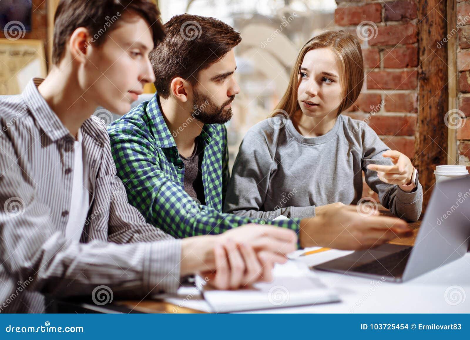 Groep toevallige bedrijfsmensen die aan nieuw project werken Zij die laptop met behulp van en bespreken over concept Het oplossen
