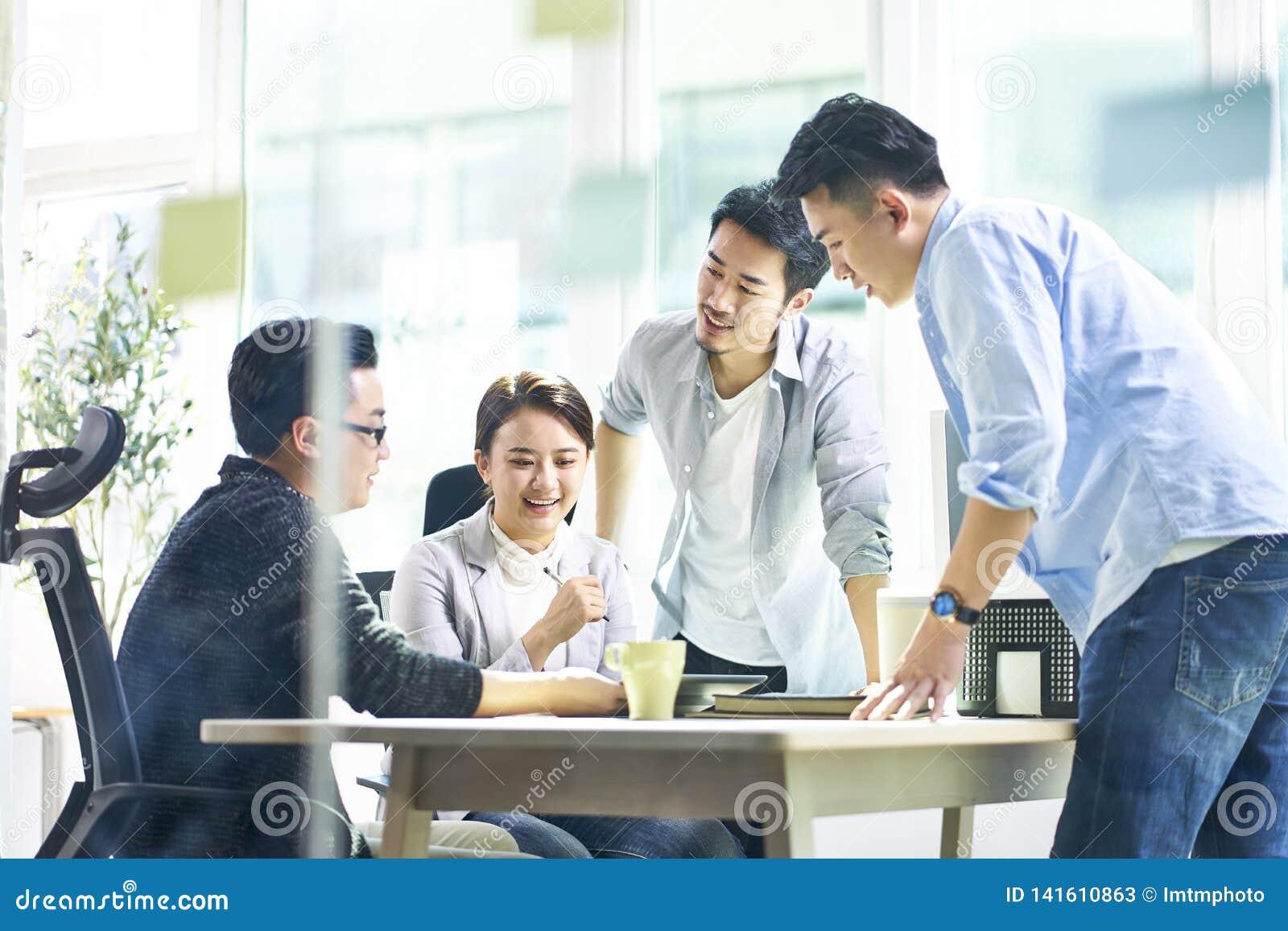 Groep van vier Aziatische teammates die samen het bespreken van zaken in bureau werken