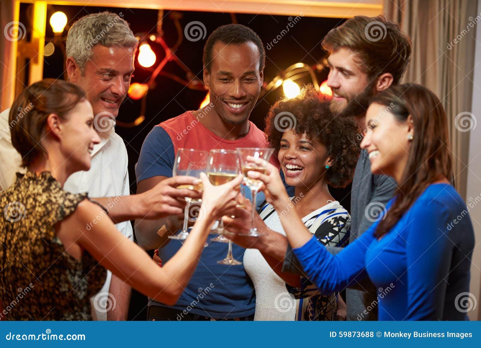 Groep volwassen vrienden bij partij die een toost maken