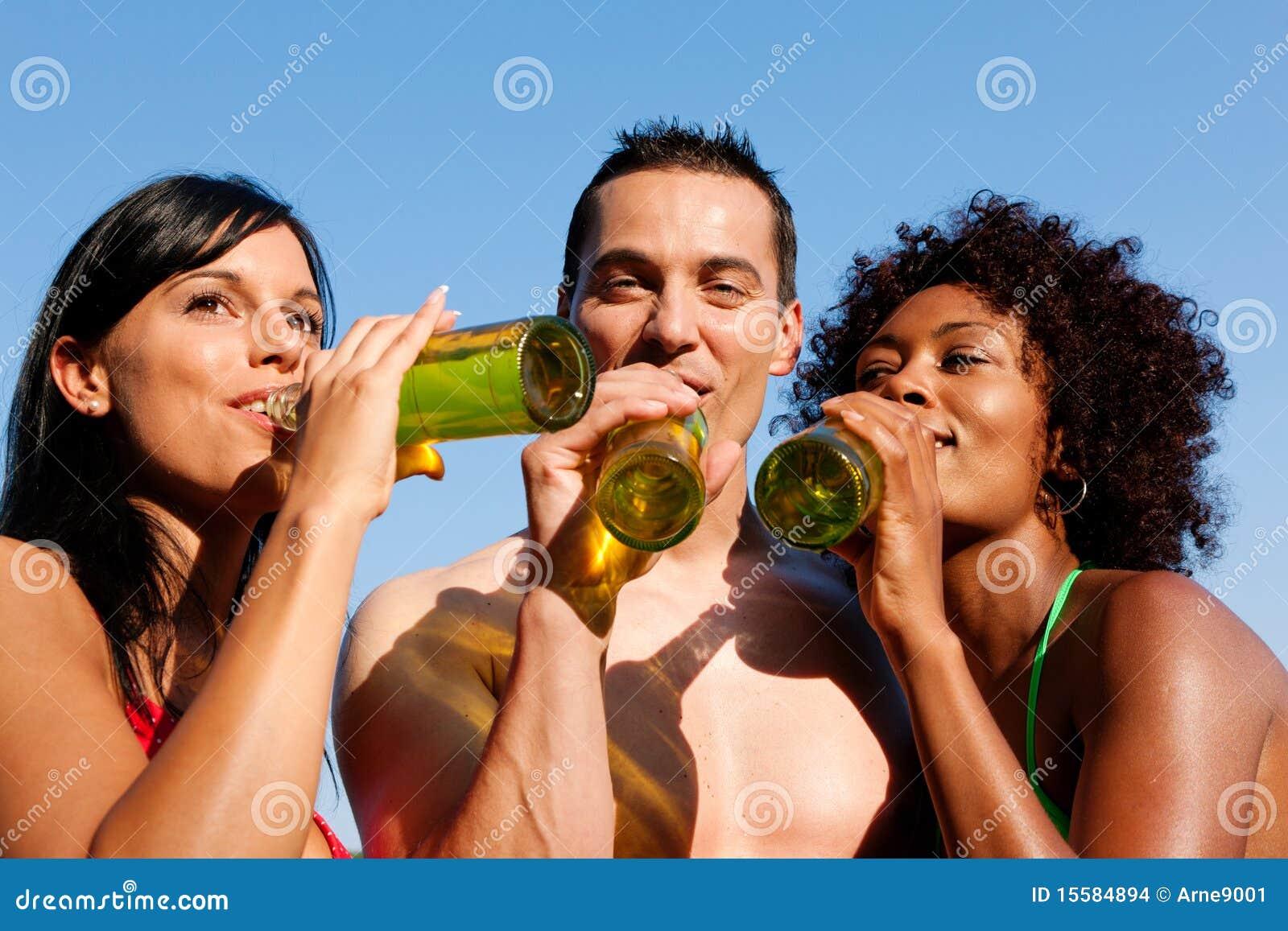 Groep vrienden die bier in swimwear drinken