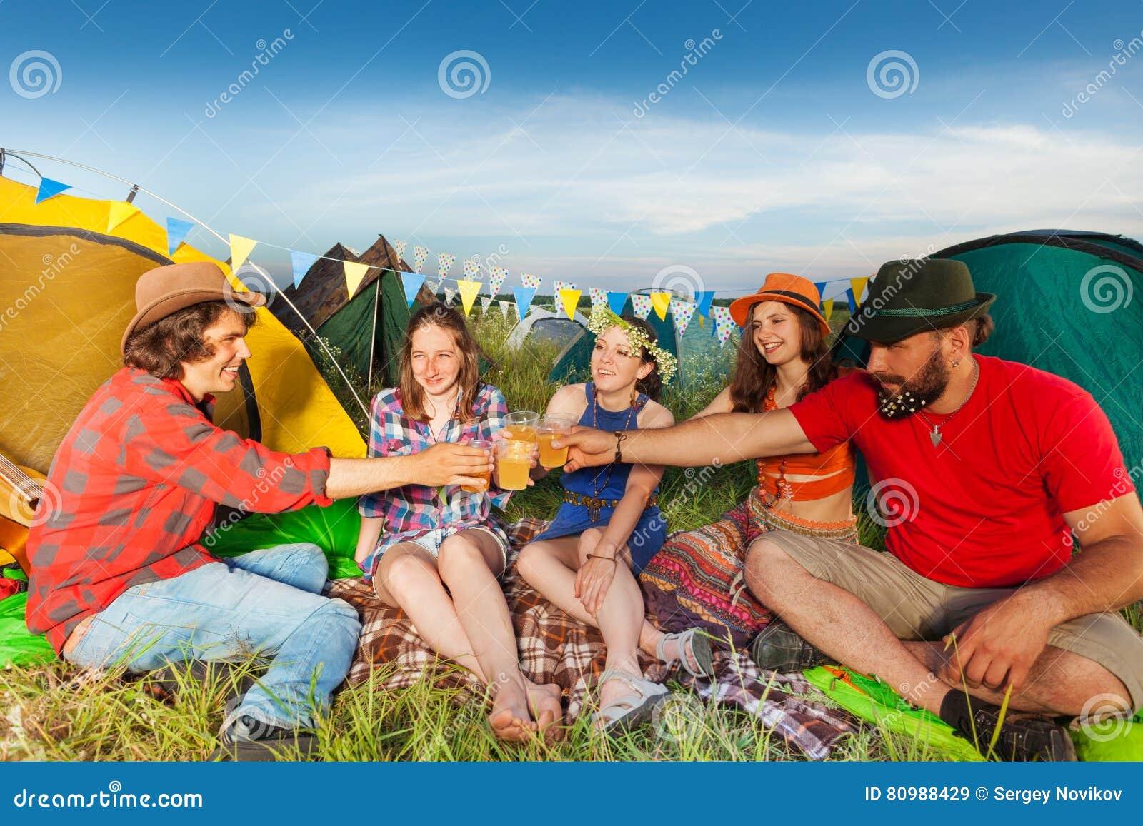 Groep vrienden die buiten hun tenten drinken