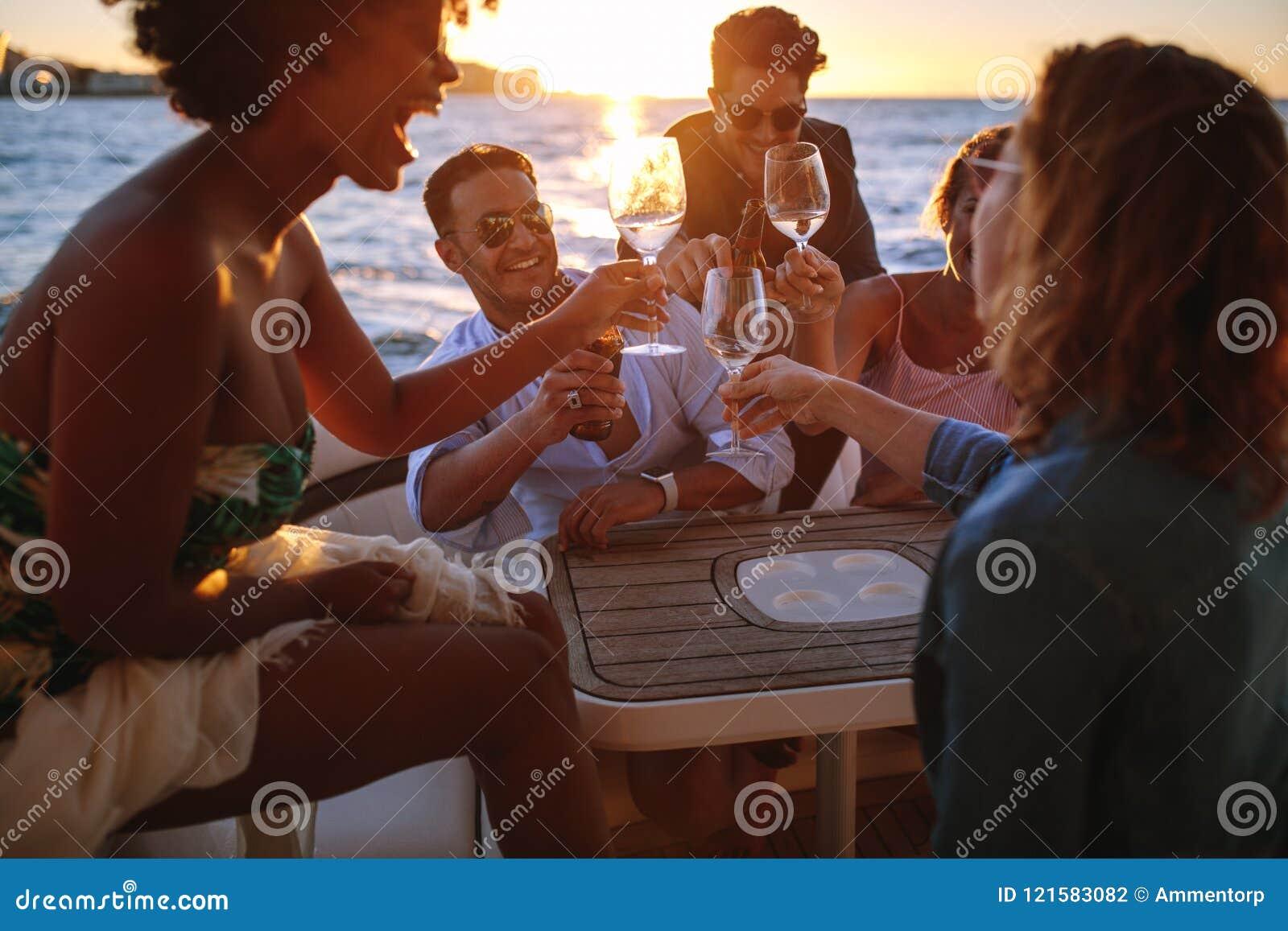 Groep vrienden die met dranken bij bootpartij toejuichen