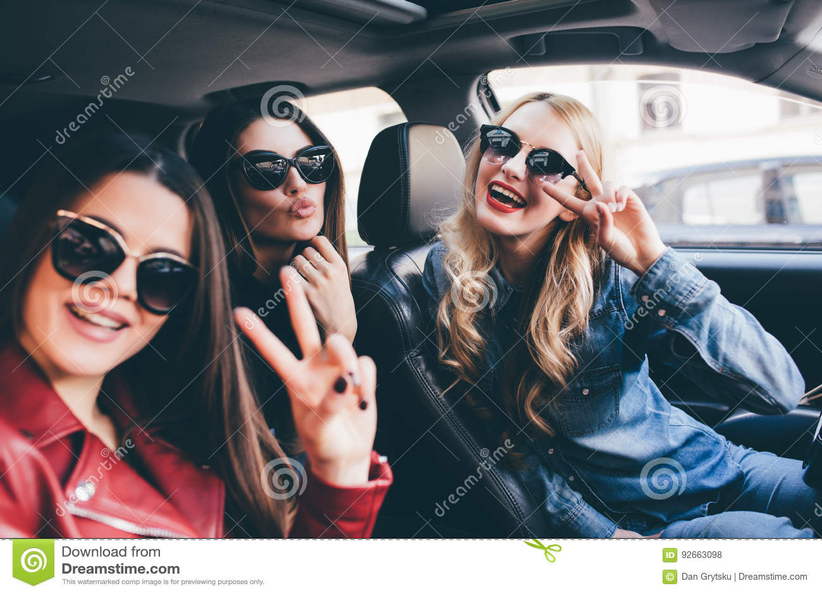 Groep vrienden die pret op de auto hebben Het zingen en het lachen in de stad