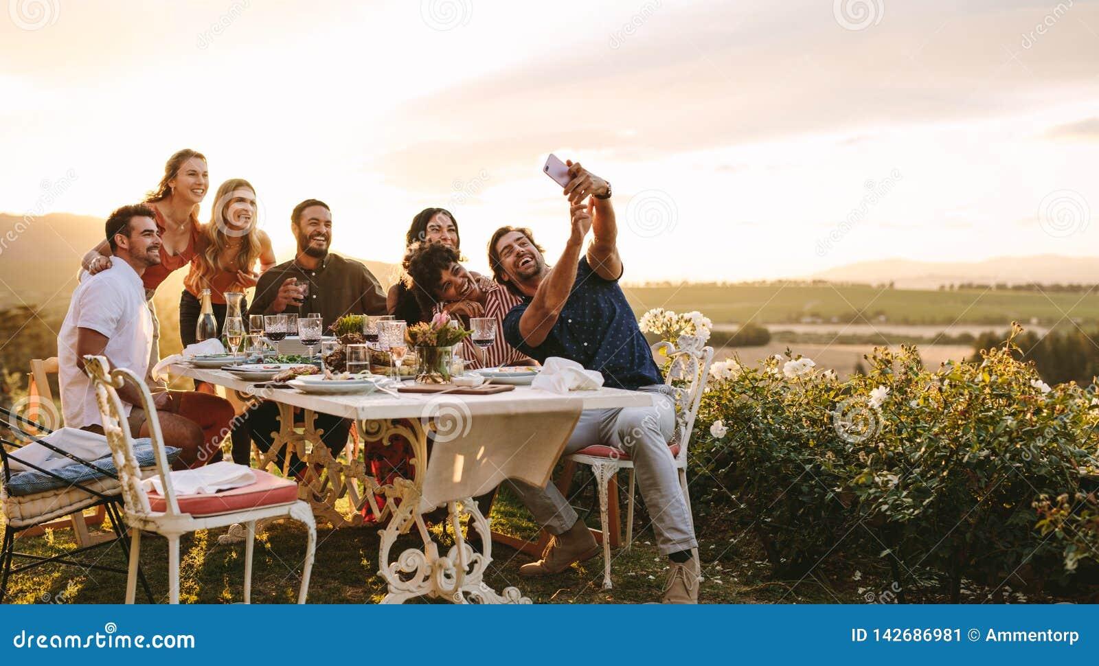 Groep vrienden die selfie bij dinerpartij nemen