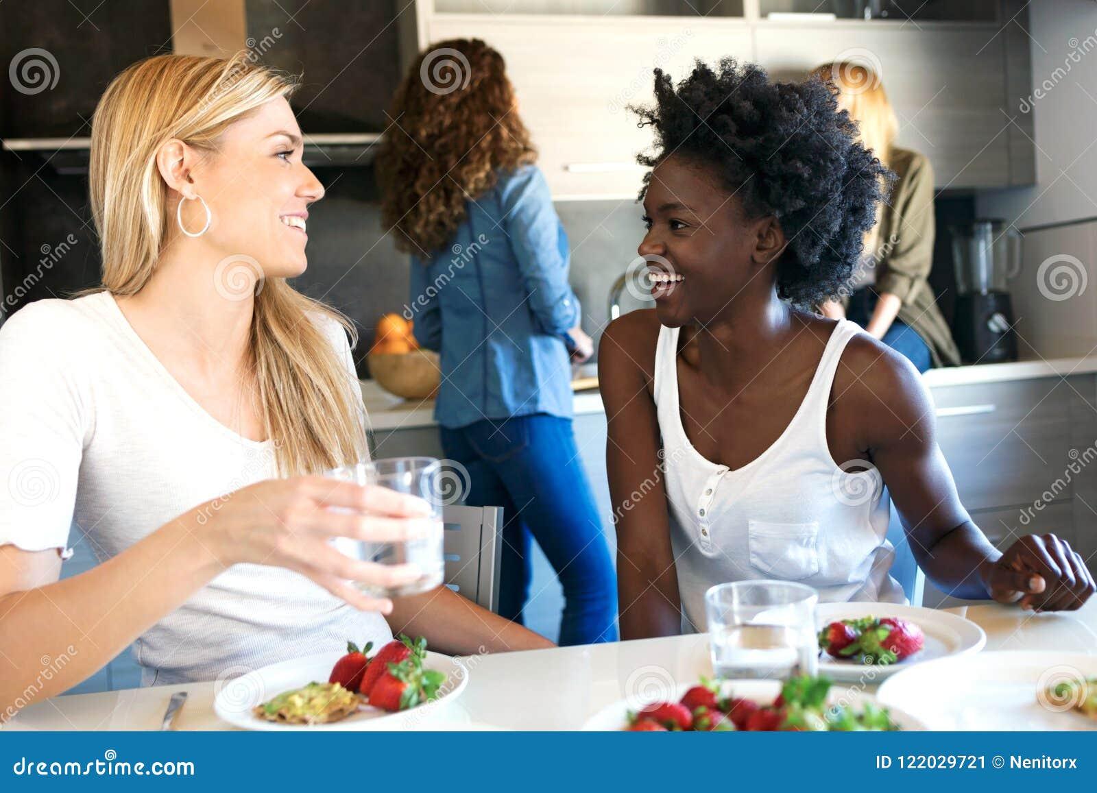 Groep vrienden die terwijl thuis het eten van gezond voedsel lachen