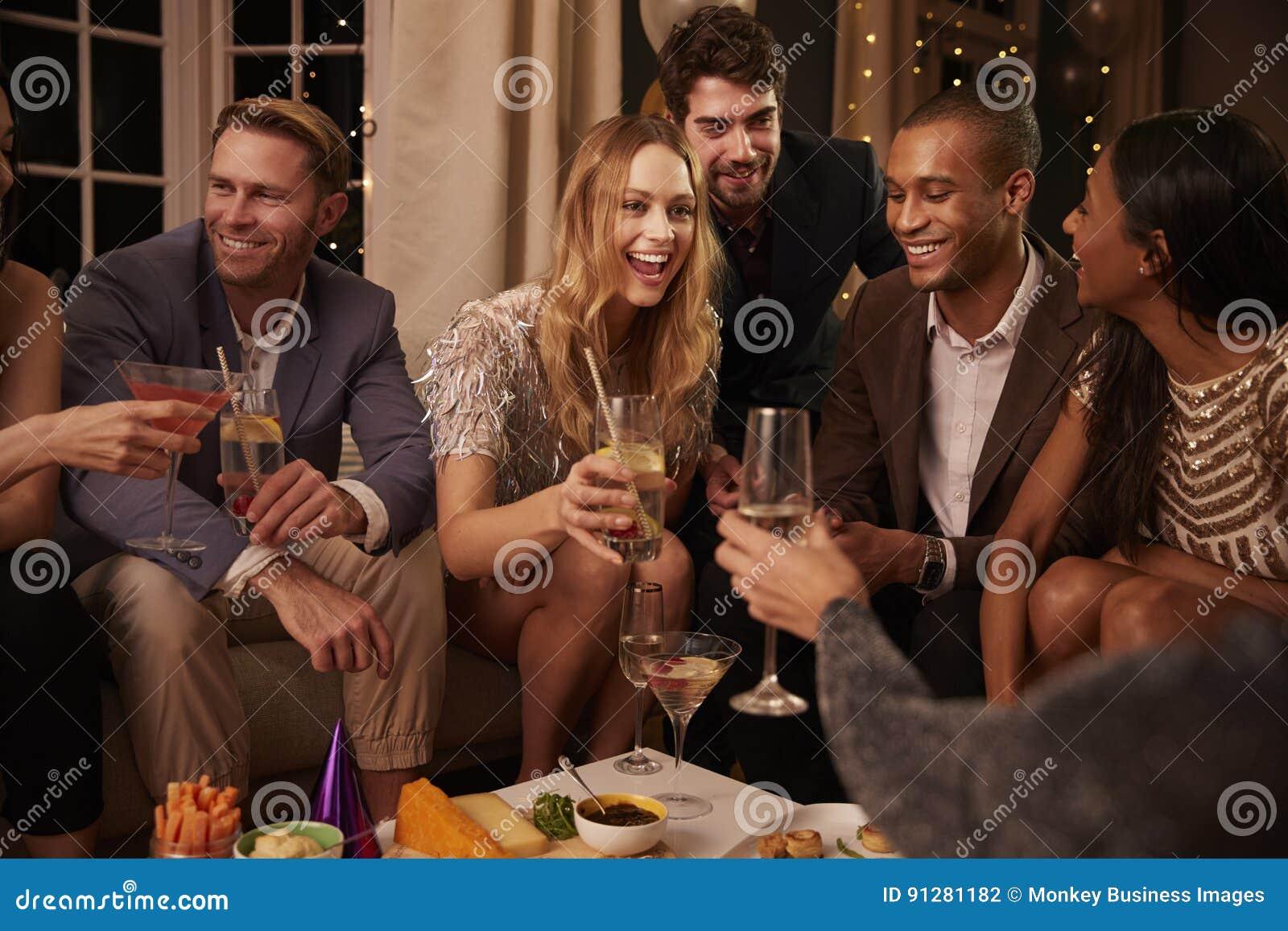 Groep Vrienden die van Dranken en Snacks genieten bij Partij