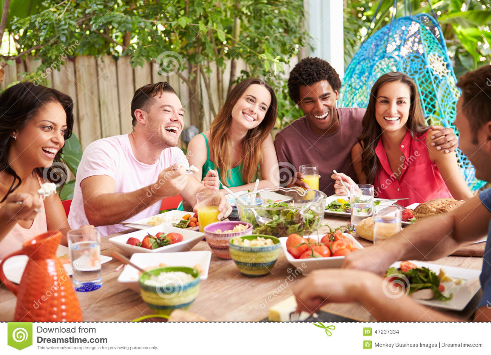 Groep Vrienden die van Maaltijd in openlucht thuis genieten