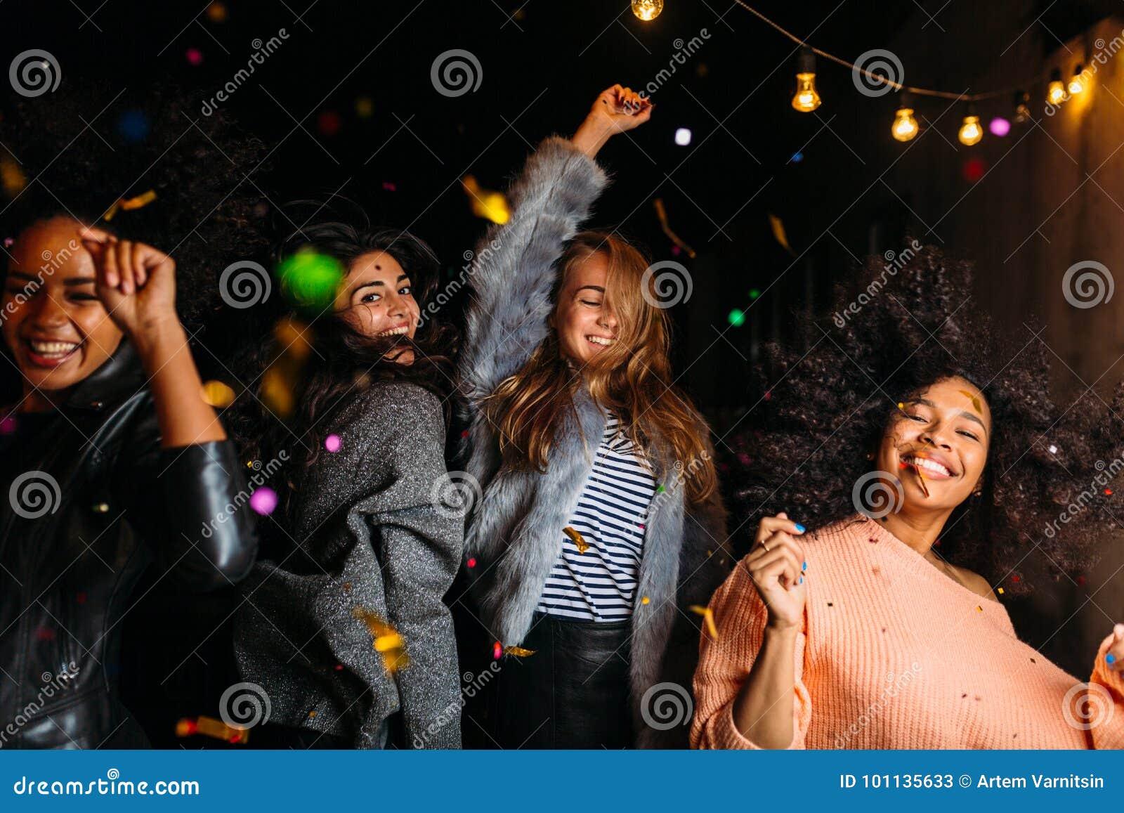 Groep vrouwelijke vrienden die bij nacht dansen