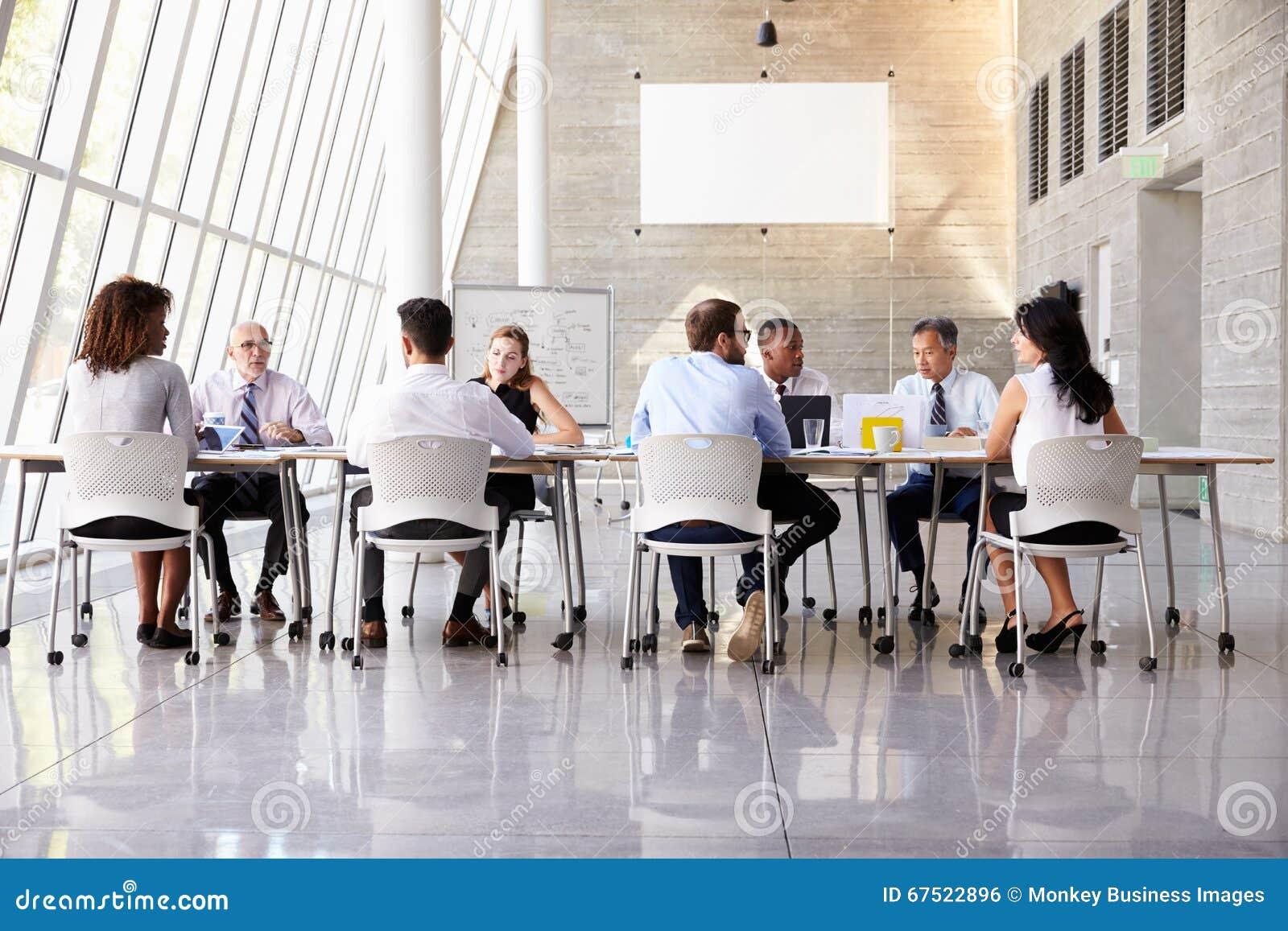 Groeps commerciële vergadering rond lijst in modern bureau stock