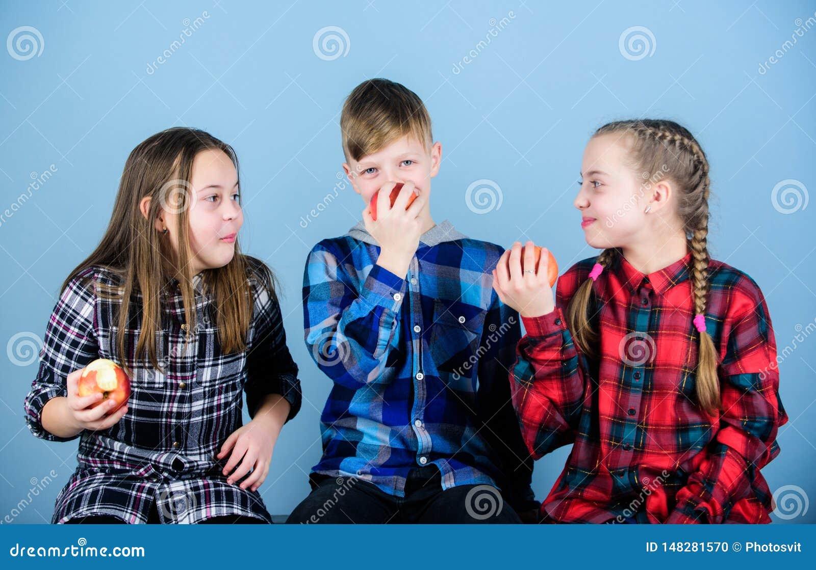 Groeps vrolijke tieners die pret hebben en appelen eten Gezonde het op dieet zijn en vitaminevoeding Jongen en meisjes de vriende