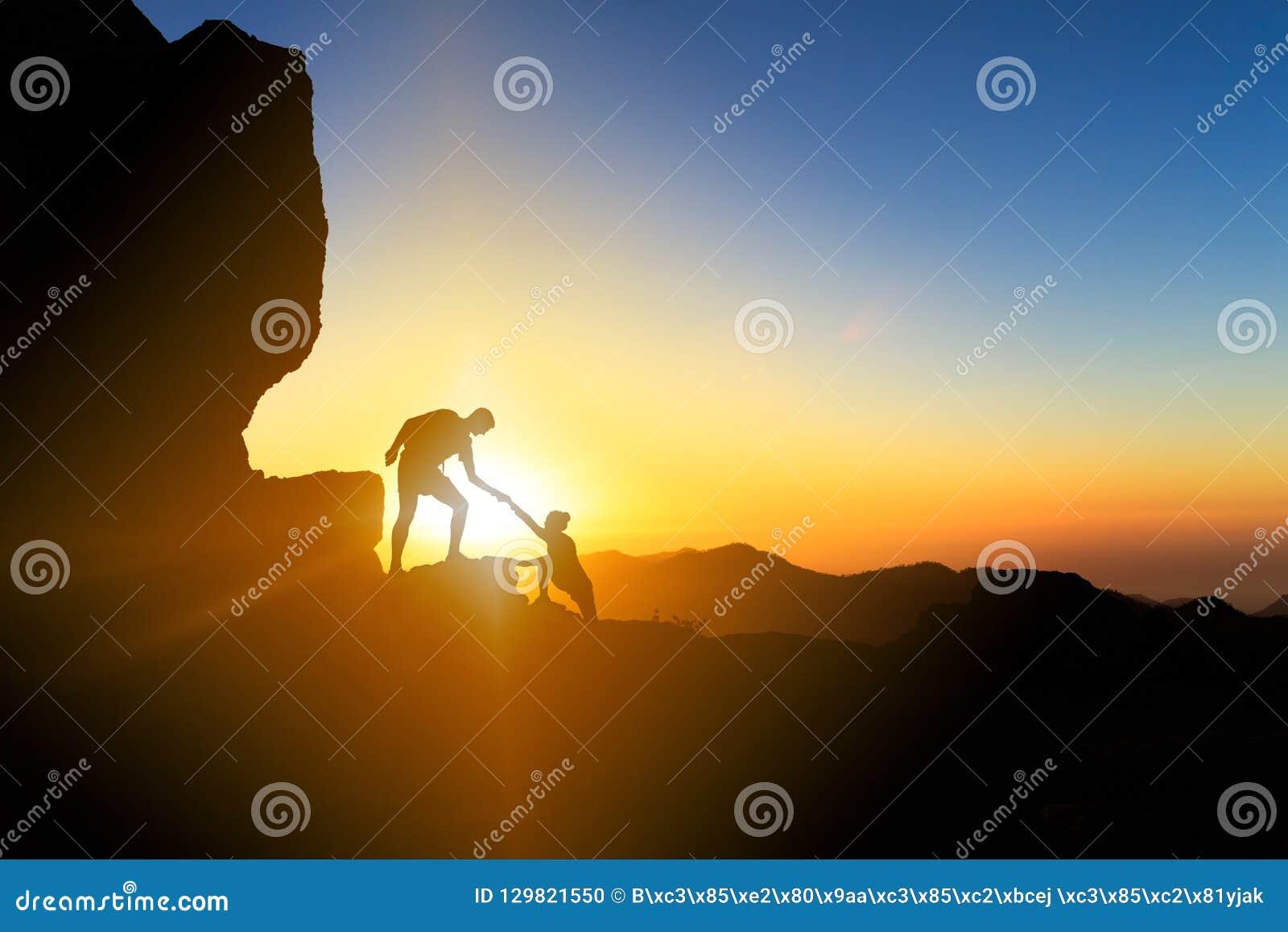 Groepswerk die hand helpen het beklimmen bij zonsondergang koppelen