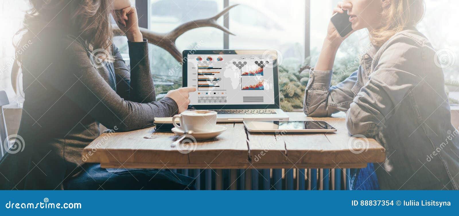 Groepswerk, twee jonge onderneemsters die over lijst van elkaar zitten Voor lijstlaptop, koffiekop en tabletcomputer