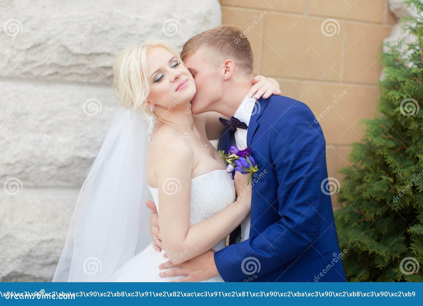 Groom нежно обнимает плеча ` s невесты