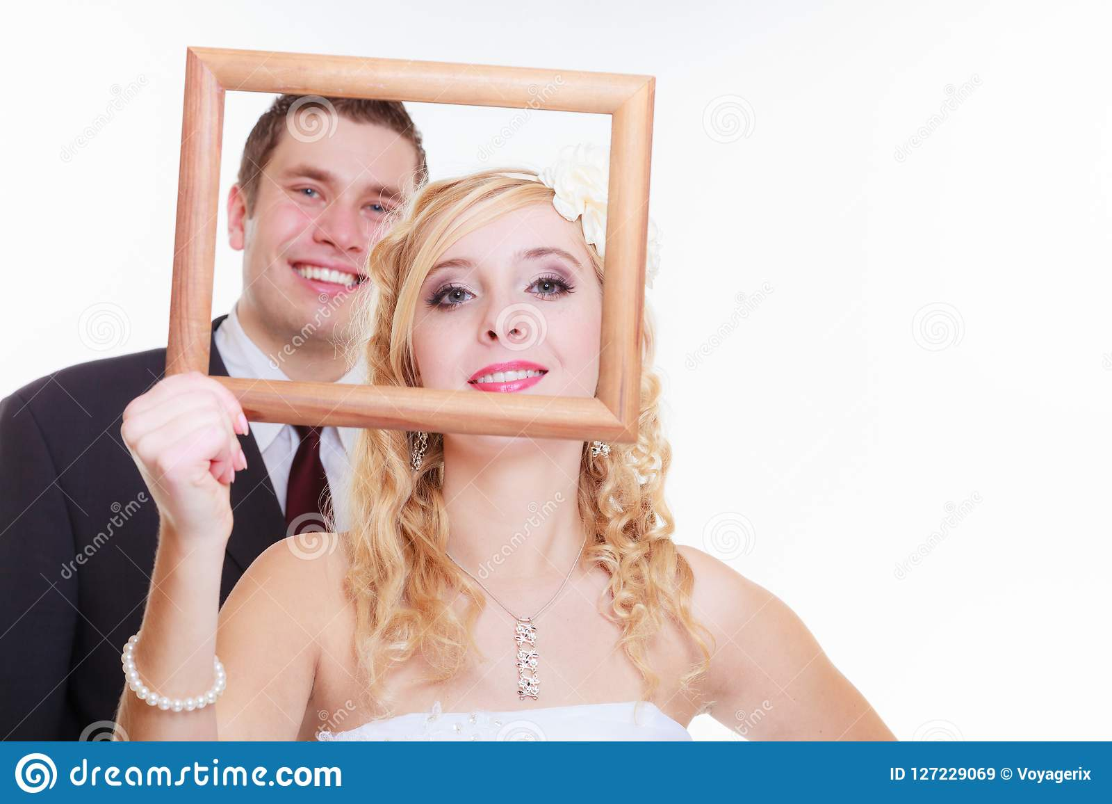 Groom and bride holding empty frame