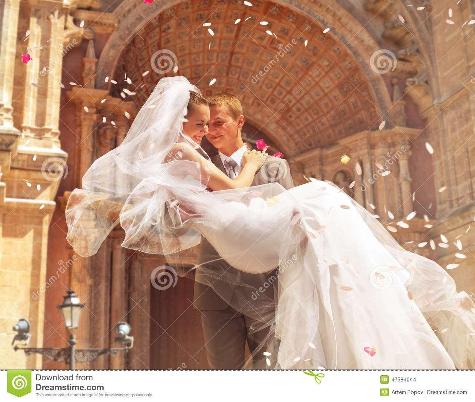 Bride And Groom Enjoying Amazing Sunset On A Beautiful: Groom Carrying Bride Near Church Stock Photo