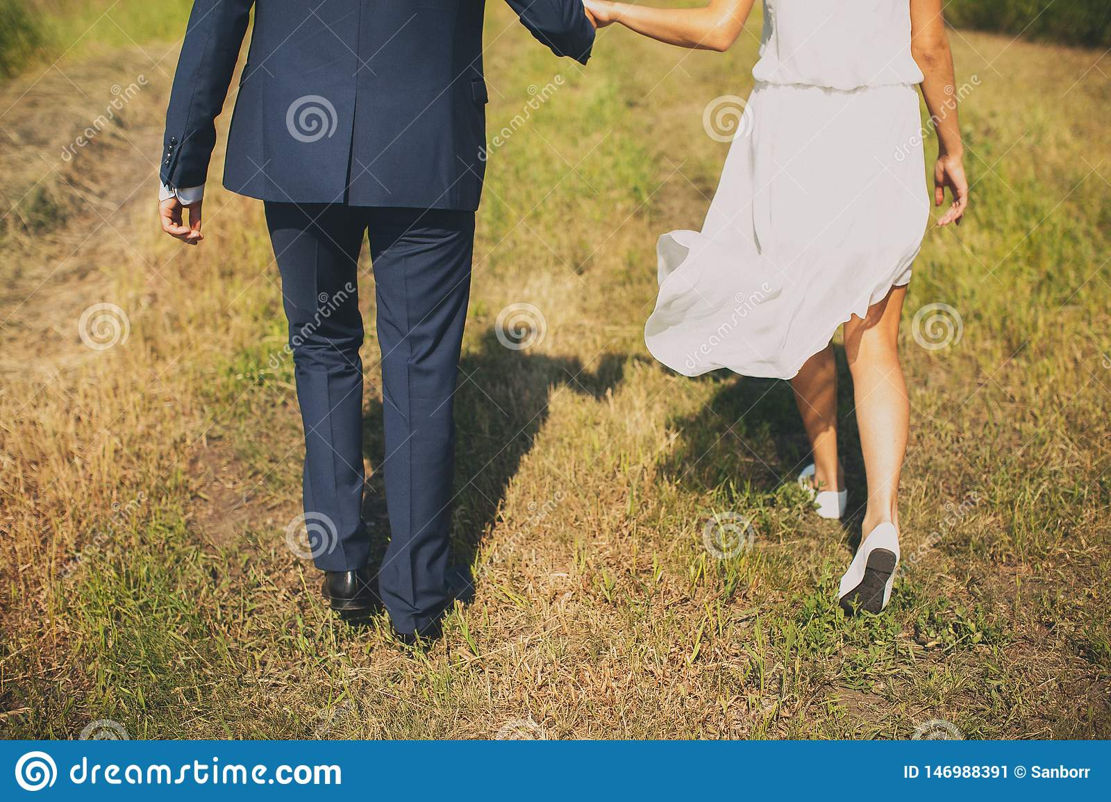 The groom in a classic suit and the bride in a short white light chiffon dress, go on the green grass, rear view. A guy and a girl