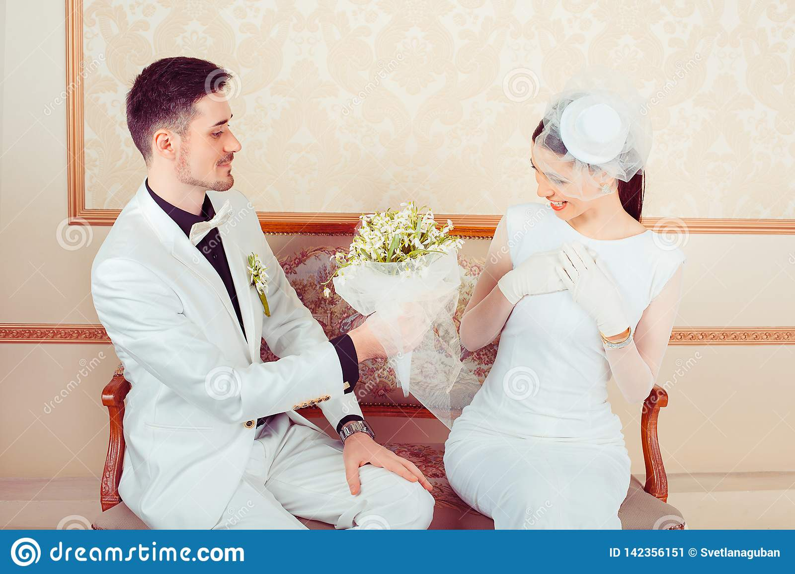 Groom giving bouquet to charming bride