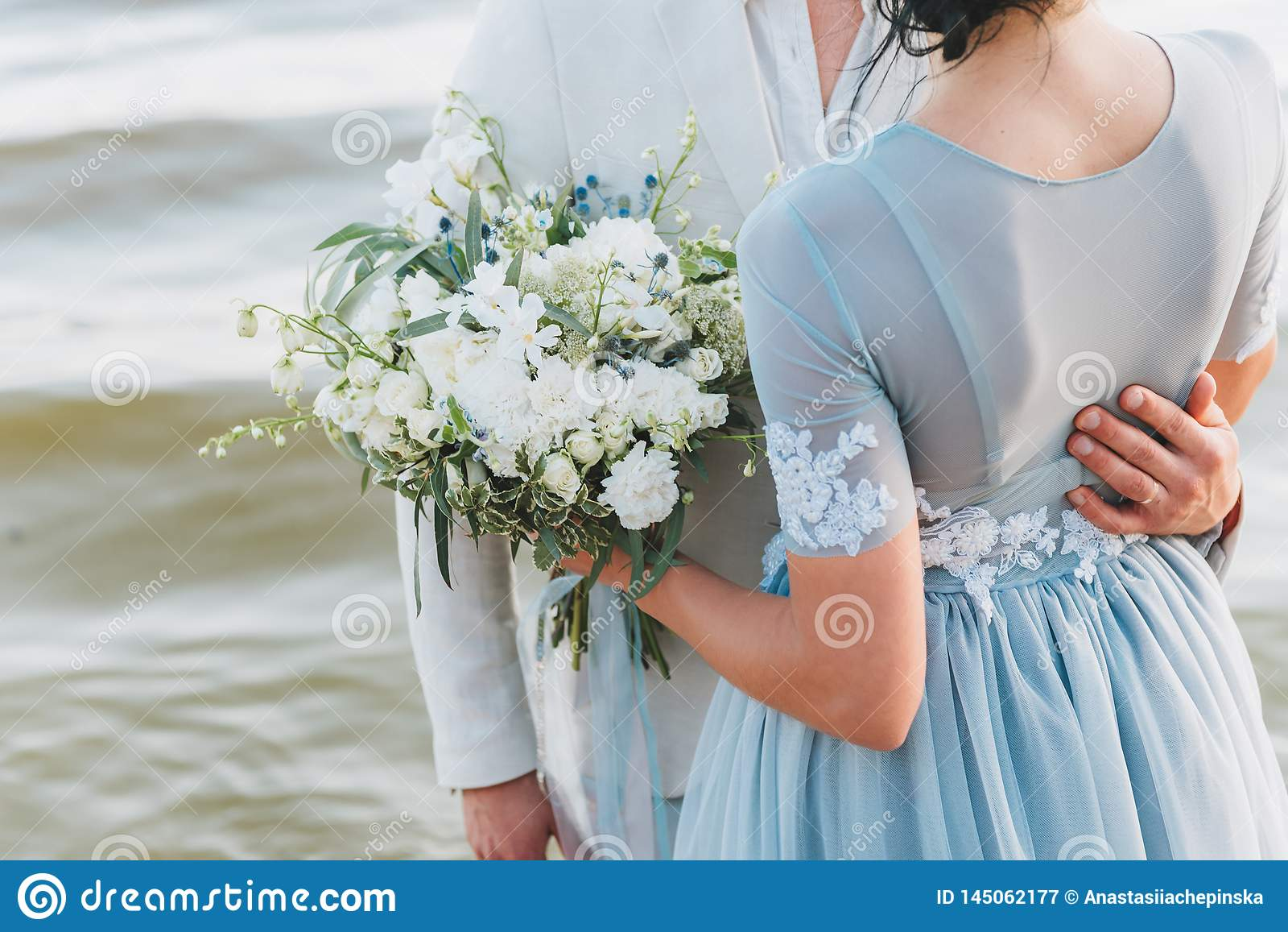 Groom having his hand on his bride`s waist, standing on a beach. Bride is holding a bouquet.