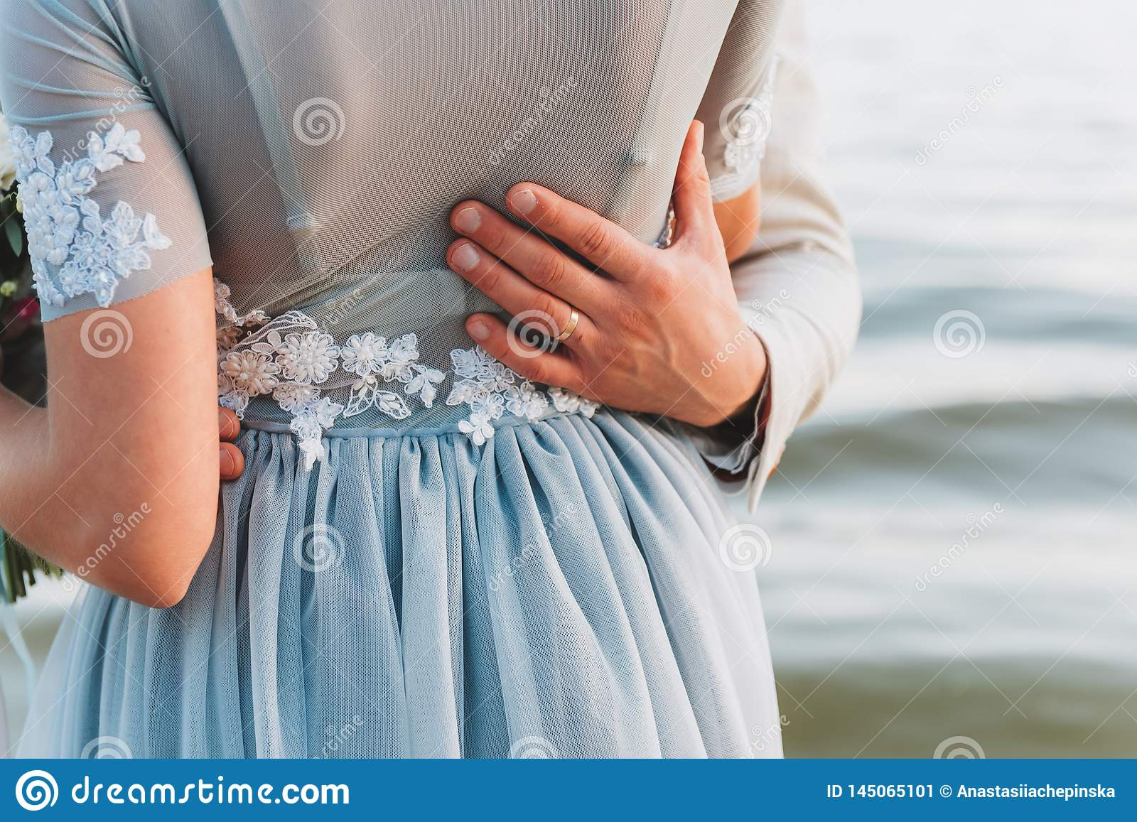 Groom having his hand on his bride`s waist, standing on a beach