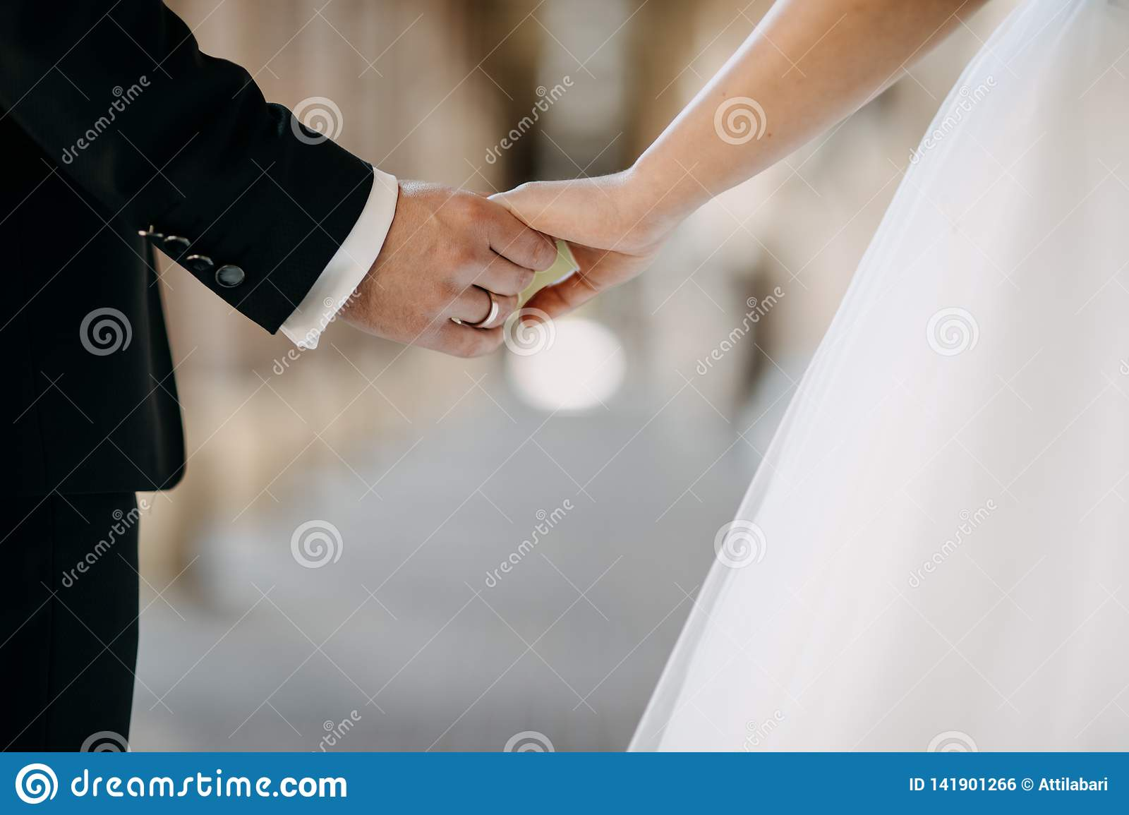 Groom holding the bride`s hand while walking