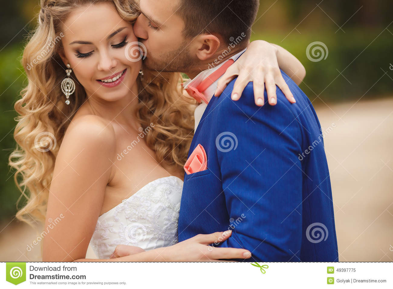 The Groom Kisses The Bride In A Green Park In The Summer Stock Photo