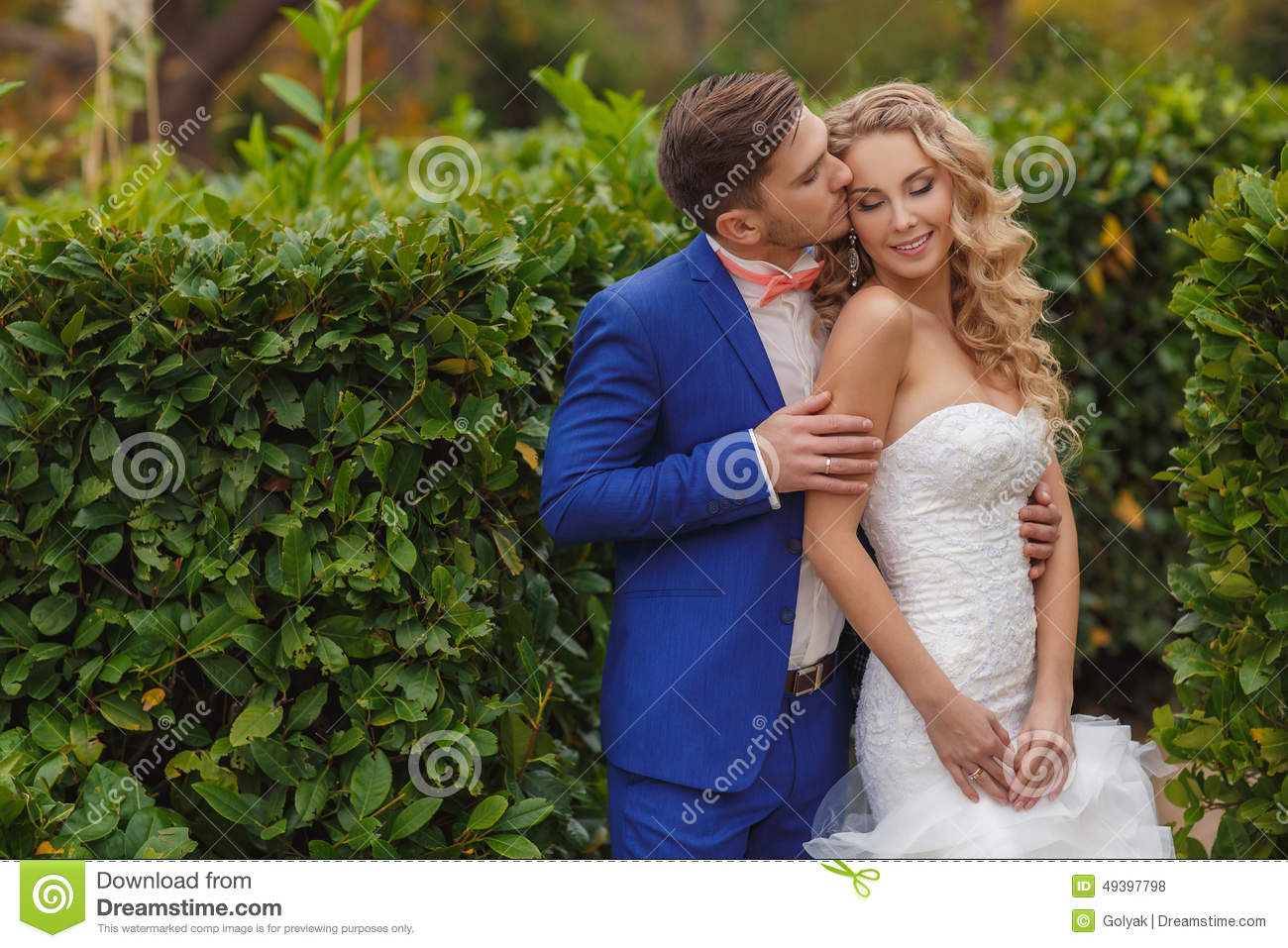 The Groom Kisses The Bride In A Green Park In The Summer. Stock ...