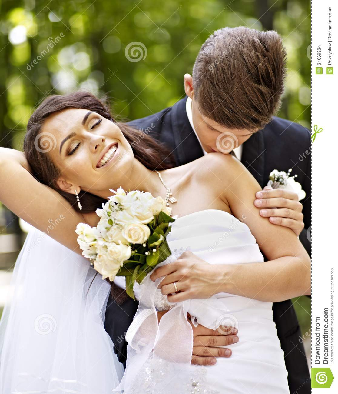 Groom Kissing Bride On Shoulder Stock