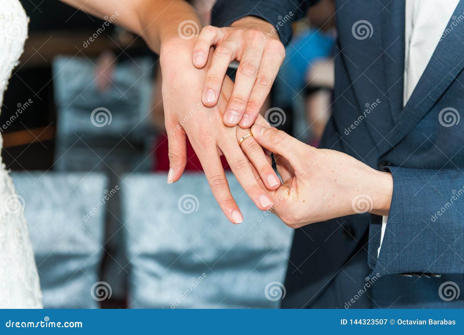 Wedding rings on hands of newlyweds