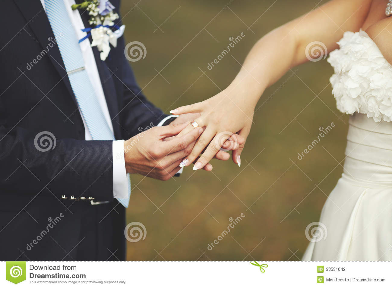 Groom Put A Wedding Ring On Finger Of His Lovely Bride Stock Photo