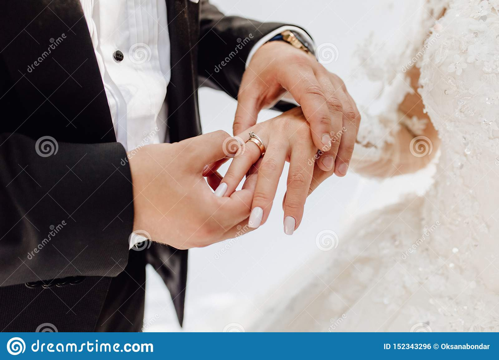 Groom Putting Jewelry Golden Ring On Bride Finger Stock Photo
