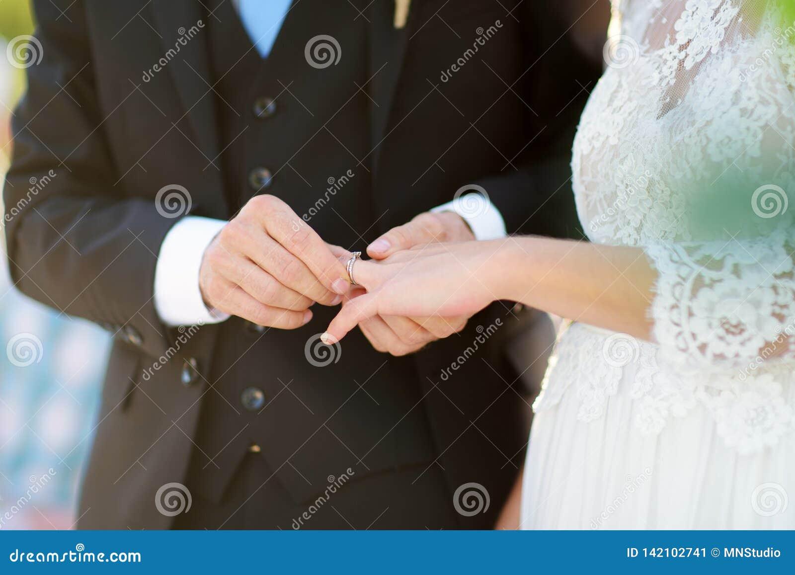 Groom Putting Wedding Ring On Bride S Finger During Wedding