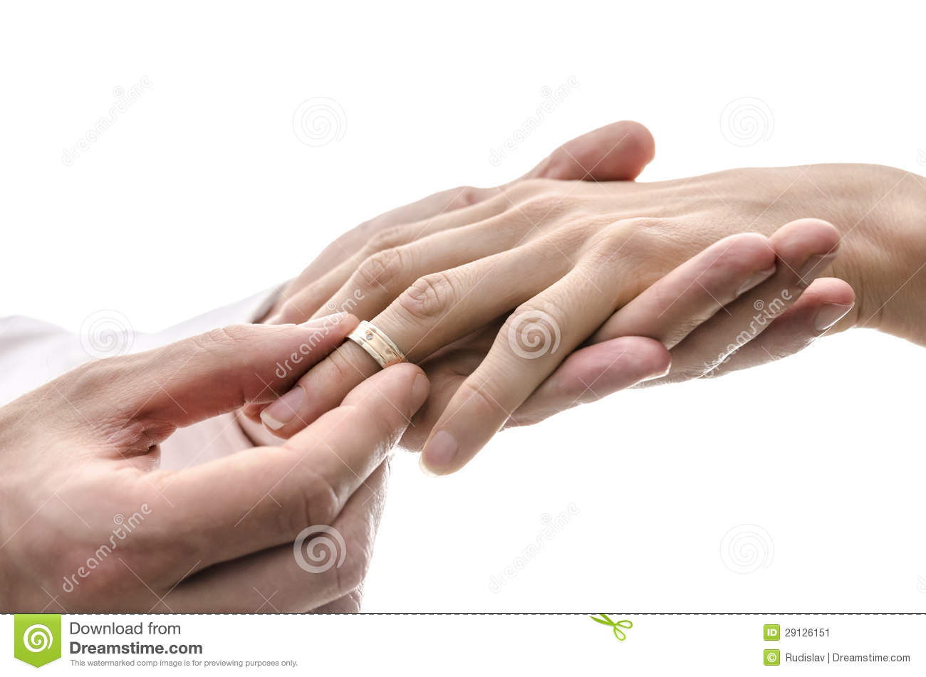 Groom Putting A Wedding Ring On The Finger Of The Bride