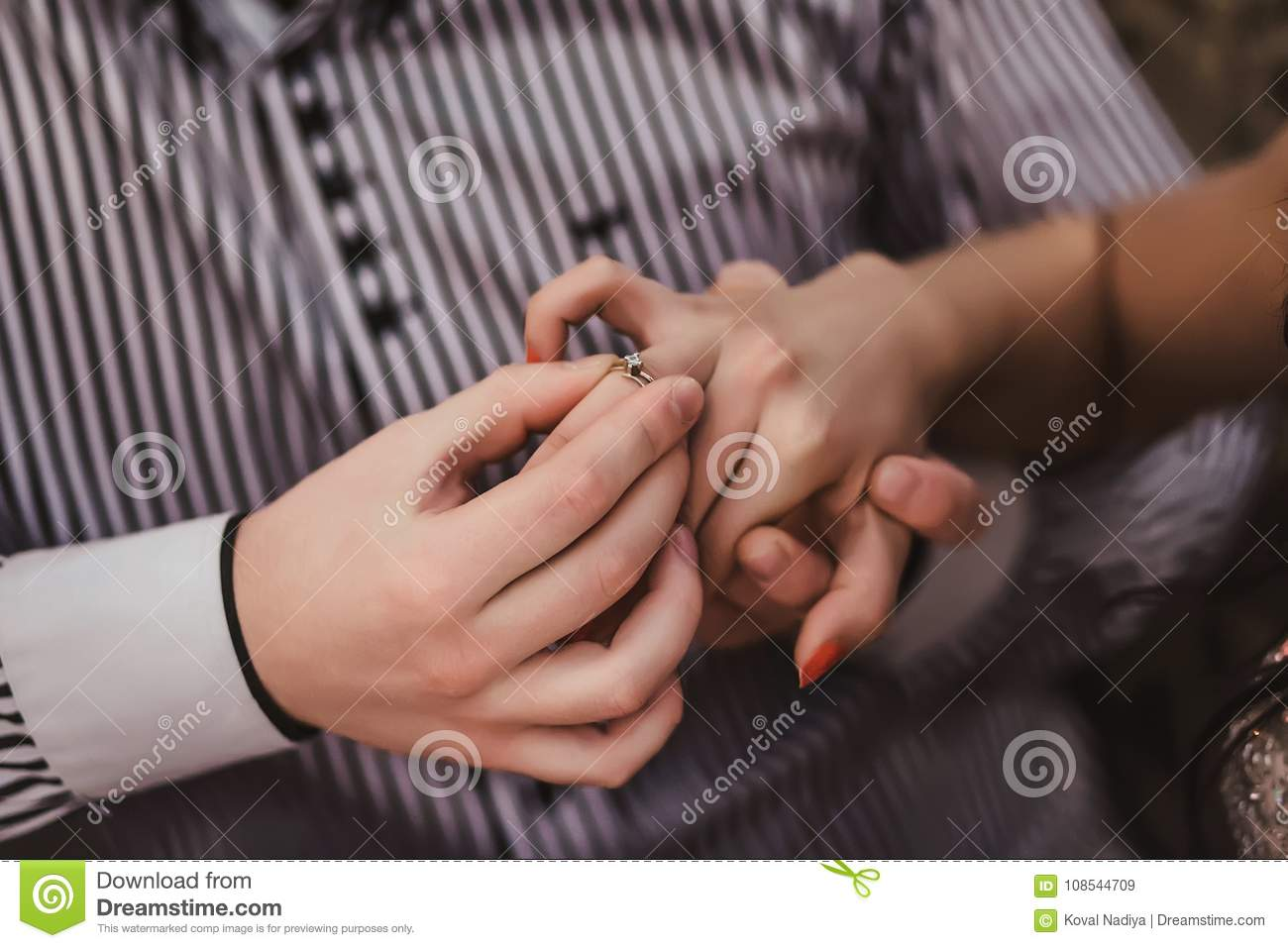 Groom S Hand Putting A Wedding Ring On The Bride S Finger