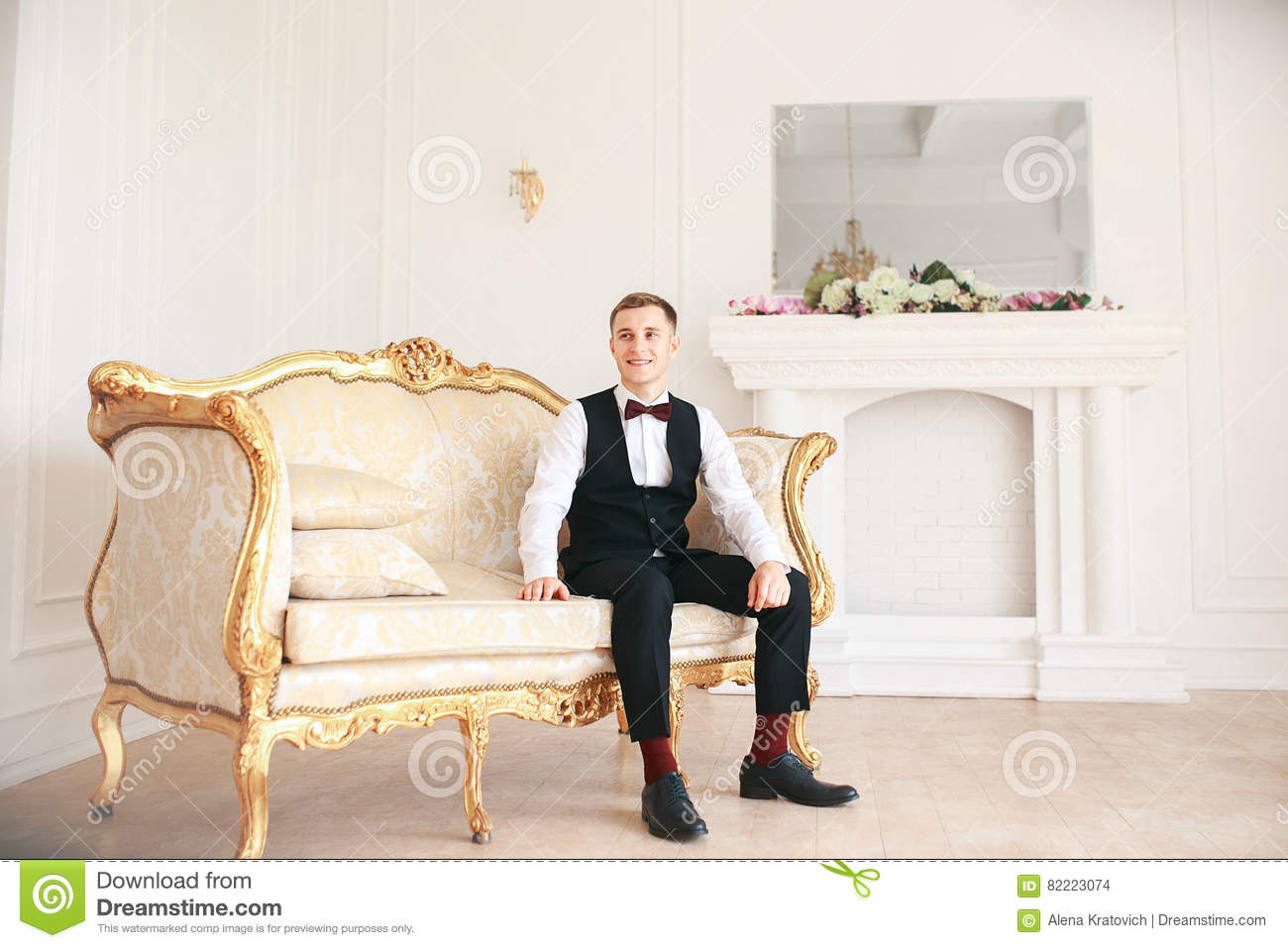 Groom sitting on the sofa waiting for the bride on his wedding day. at wedding tuxedo smiling and waiting for bride.Elegant man
