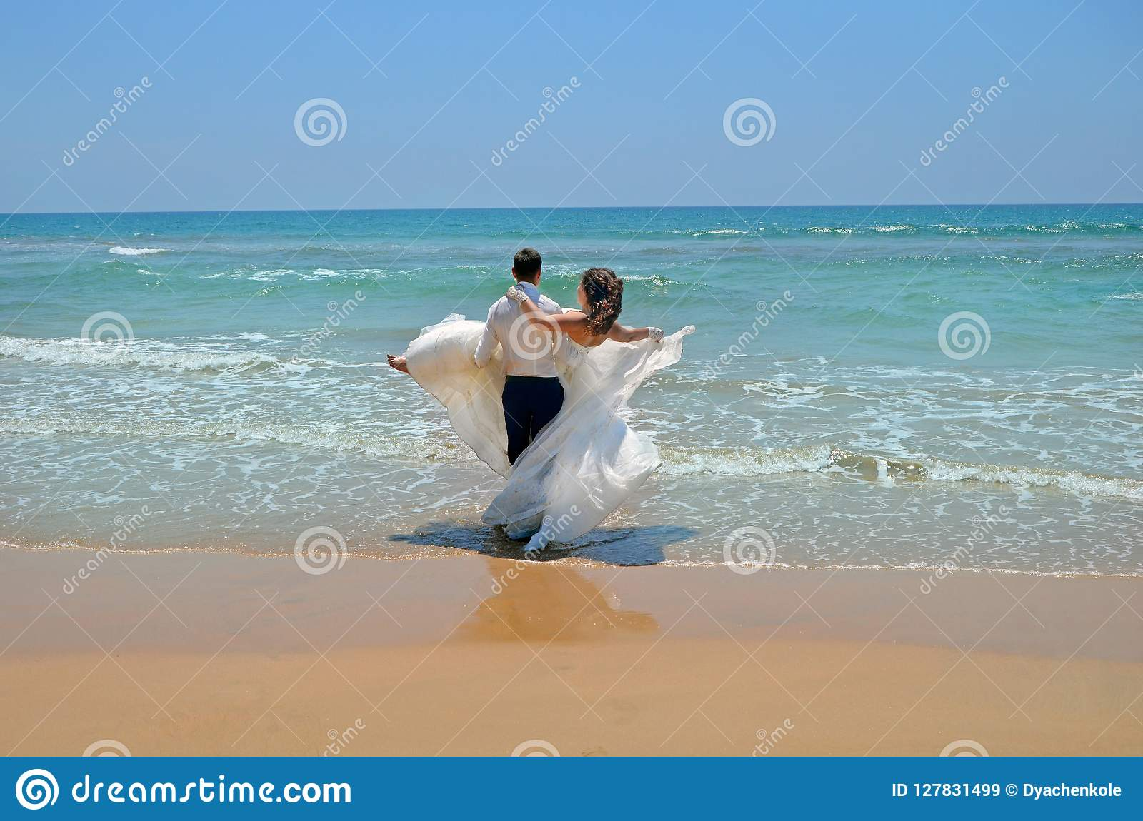 The groom in a suit carries on his hands the bride in a wedding dress in the waters of the Indian Ocean. Wedding and honeymoon